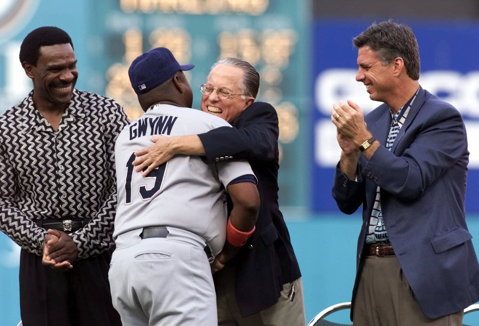 San Diego Padres legend Tony Gwynn (19) embraces Bill Beck, the Florida Marlins director of team travel, as former Cubs slugger Andre Dawson, left, and Marlins general manager David Dombrowski look on as Gwynn is honored by the Marlins during a pre-game ceremony Saturday, Aug. 25, 2001, in Miami.