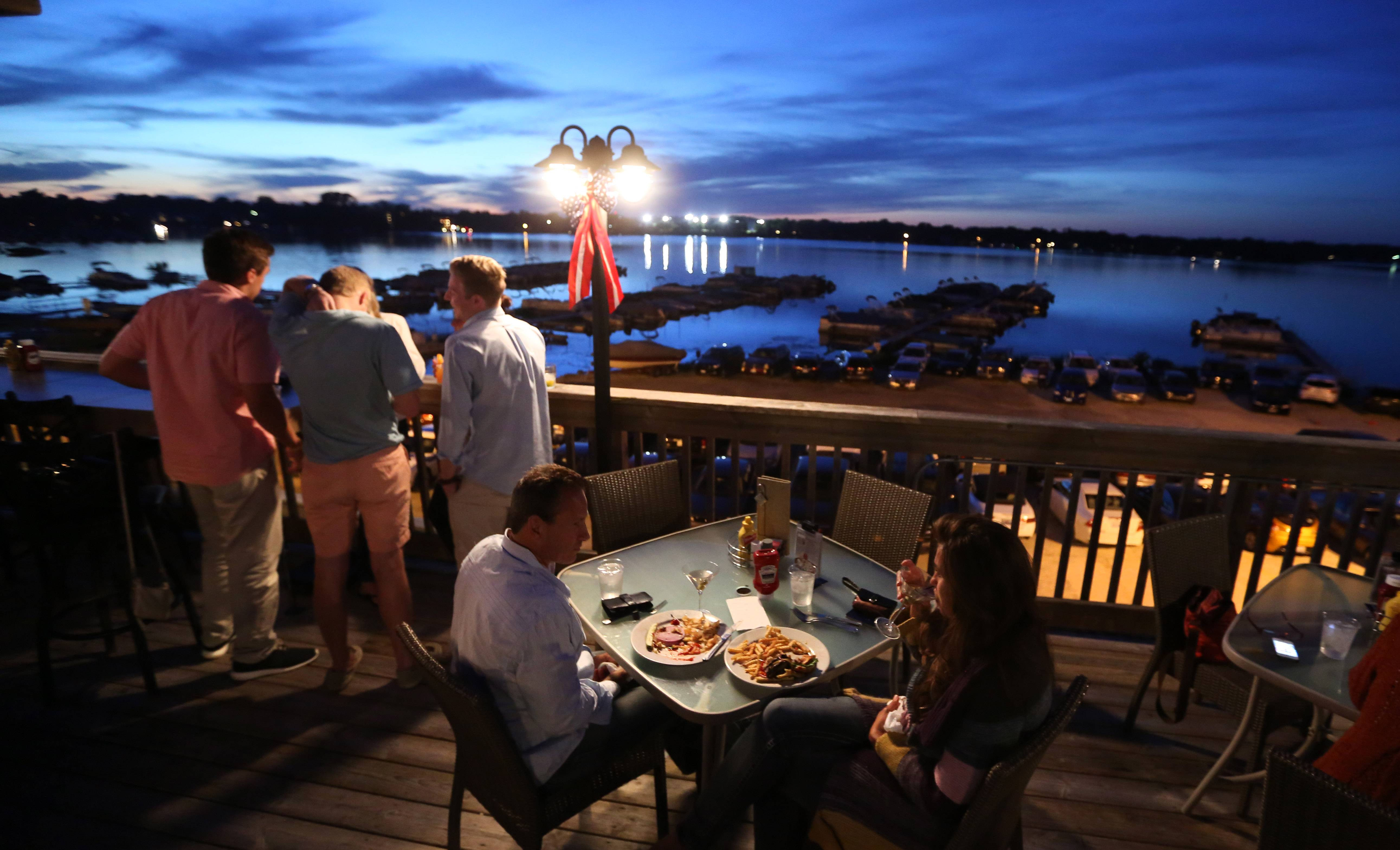 Patrons enjoy the outdoor dining and bar area overlooking Bangs Lake at Docks Bar and Grill in Wauconda.
