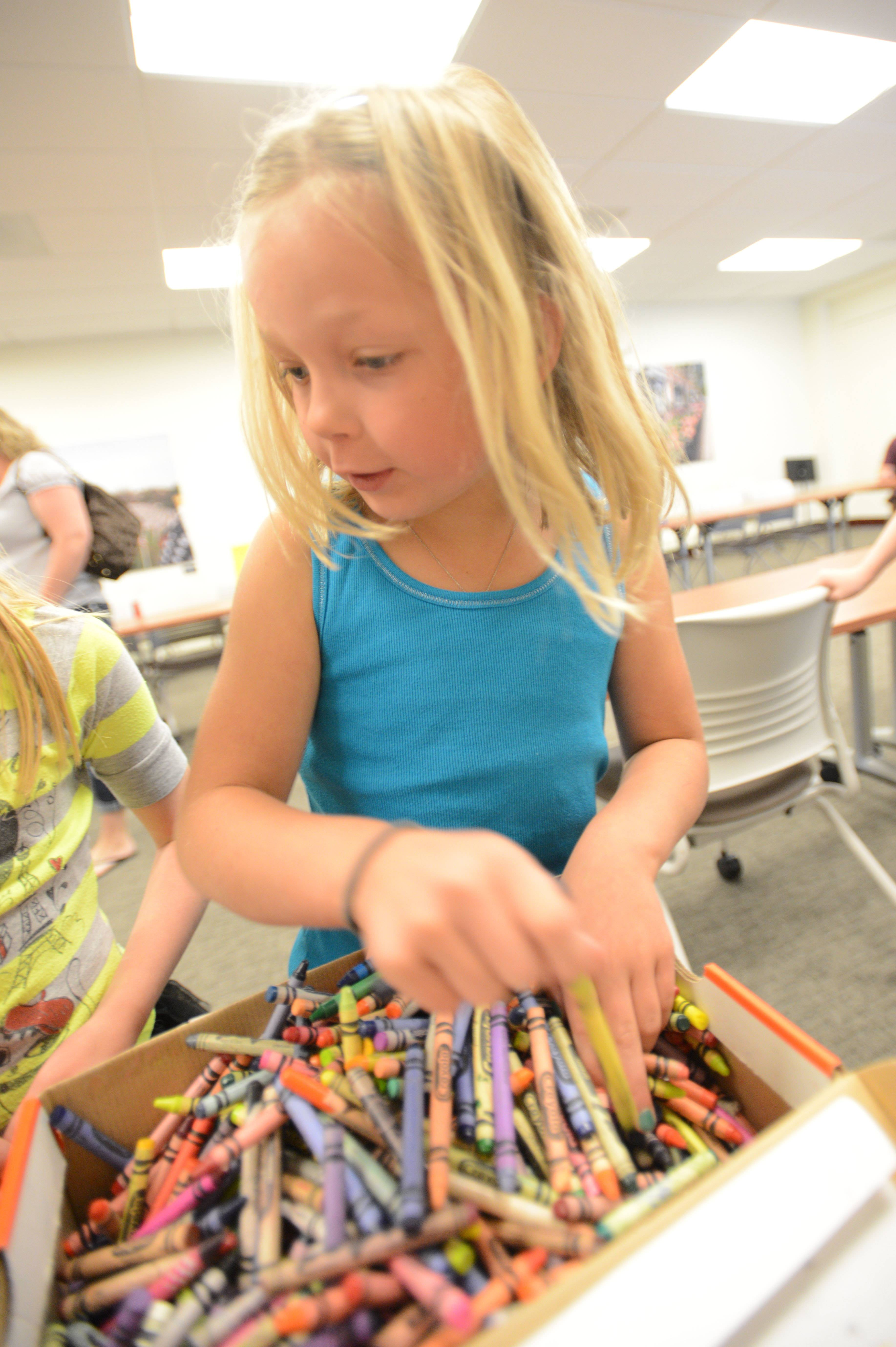 "Tori Potthoff, 7, of Aurora, sorts crayons Saturday as Kids Crew members of the Naperville-based nonprofit ""I Support Community"" peeled and sorted used and broken crayons so they can be melted down and recycled by the Glen Ellyn nonprofit SCARCE, which turns them into ""super crayons"" for people with disabilities."