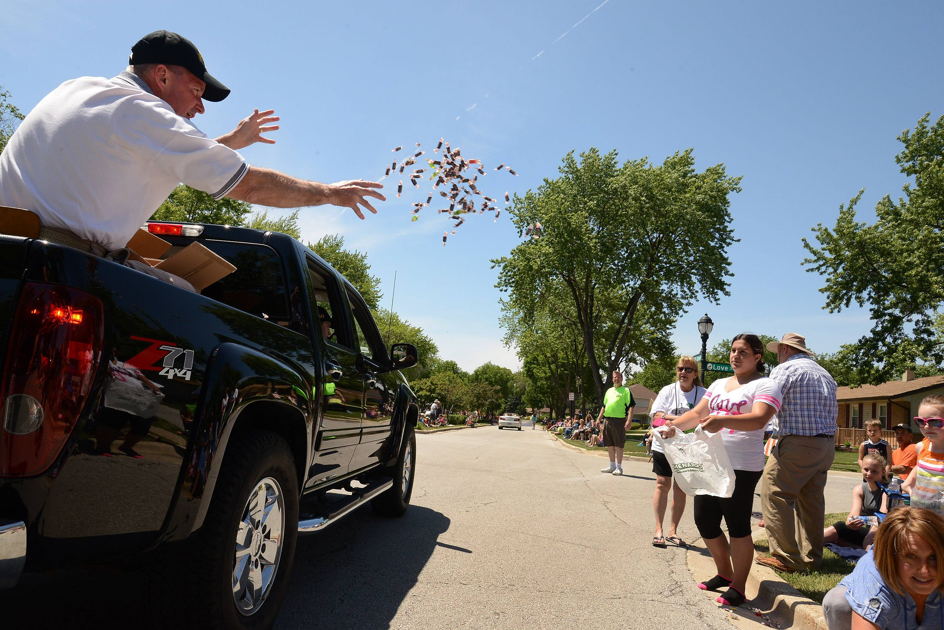 "Elk Grove Village Mayor Craig Johnson distributes candy along the parade route during the 2014 Elk Grove Village Hometown Parade Saturday. ""We're excited, we have a beautiful day, beautiful weather and expect to have great crowds, it's a great way to start summer off,"" said Mayor Craig Johnson. ""This is the first time we're doing an afternoon parade. We used to always do it at night time, six o'clock, but the crowds weren't so good, so were going to try it in the afternoon and see what happens."""