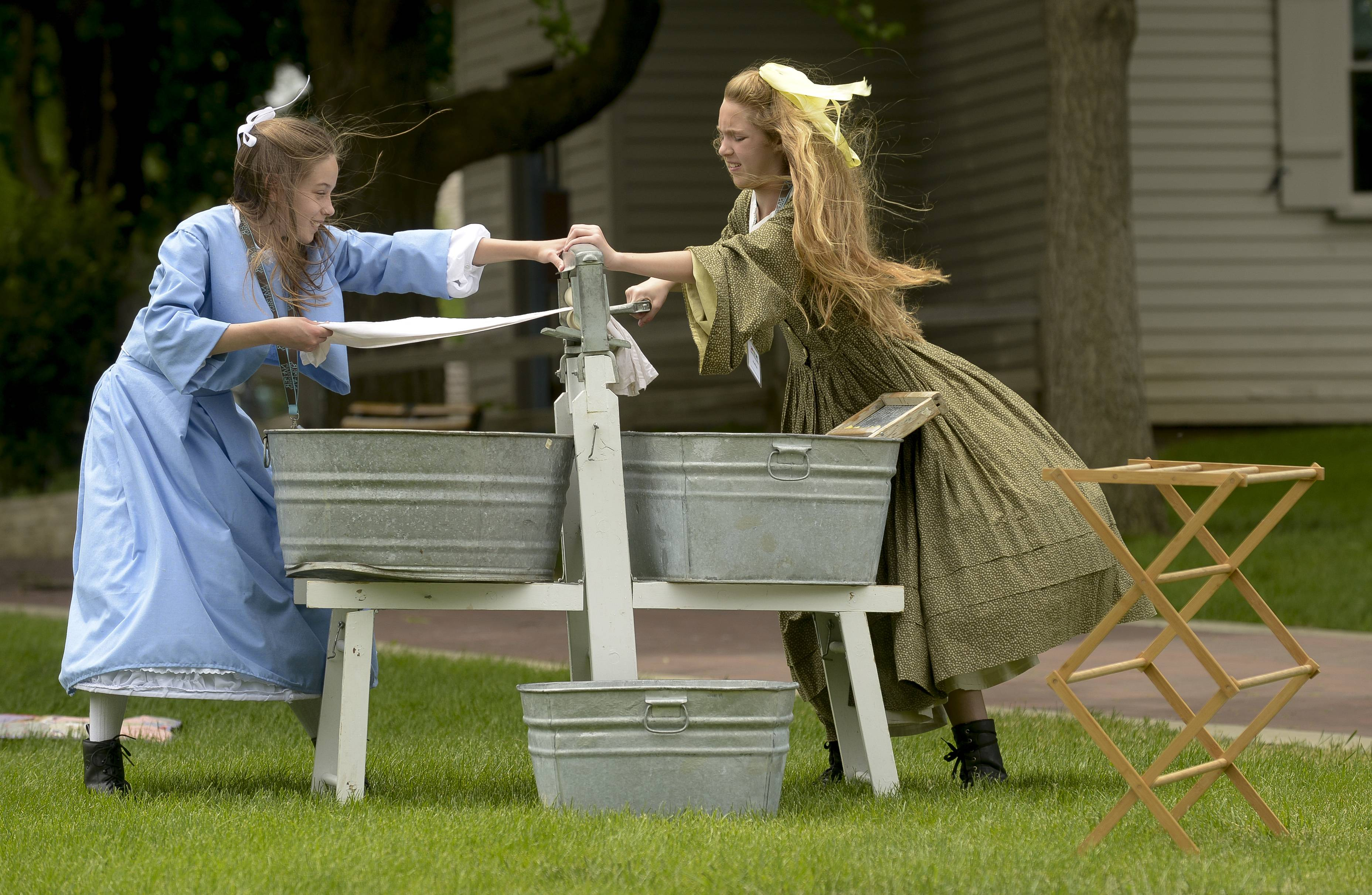 Caroline Schwinn and Julia Boffa, both 12, of Naperville, demonstrate how to wash clothing with a washboard and hand cranked wringer, as the Naper Settlement kicks off Settlement Sundays.