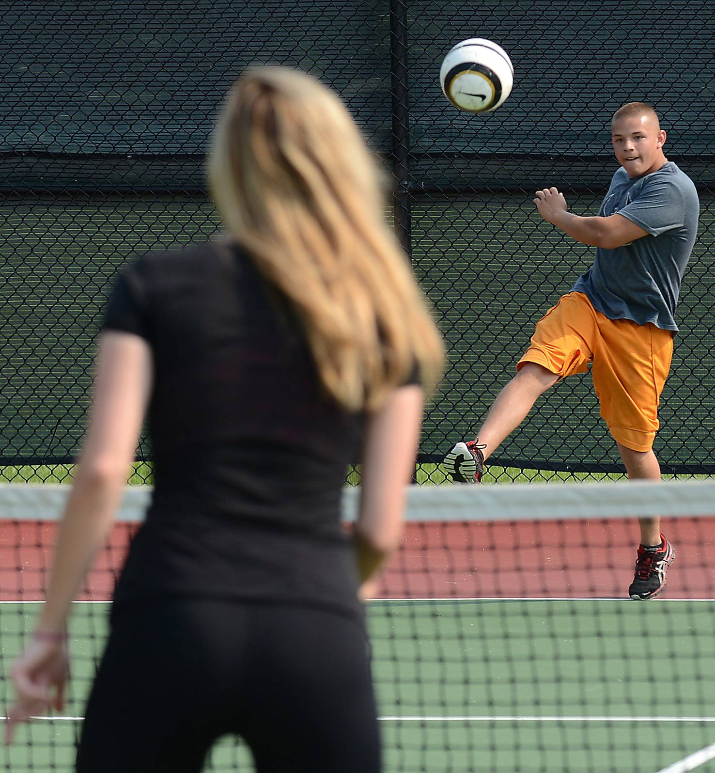 Jacob Metoyer, of South Elgin, and Amanda Soukup, of St. Charles, play their own form of tennis with a soccer ball at Primrose Farm Park in St. Charles Monday afternoon.