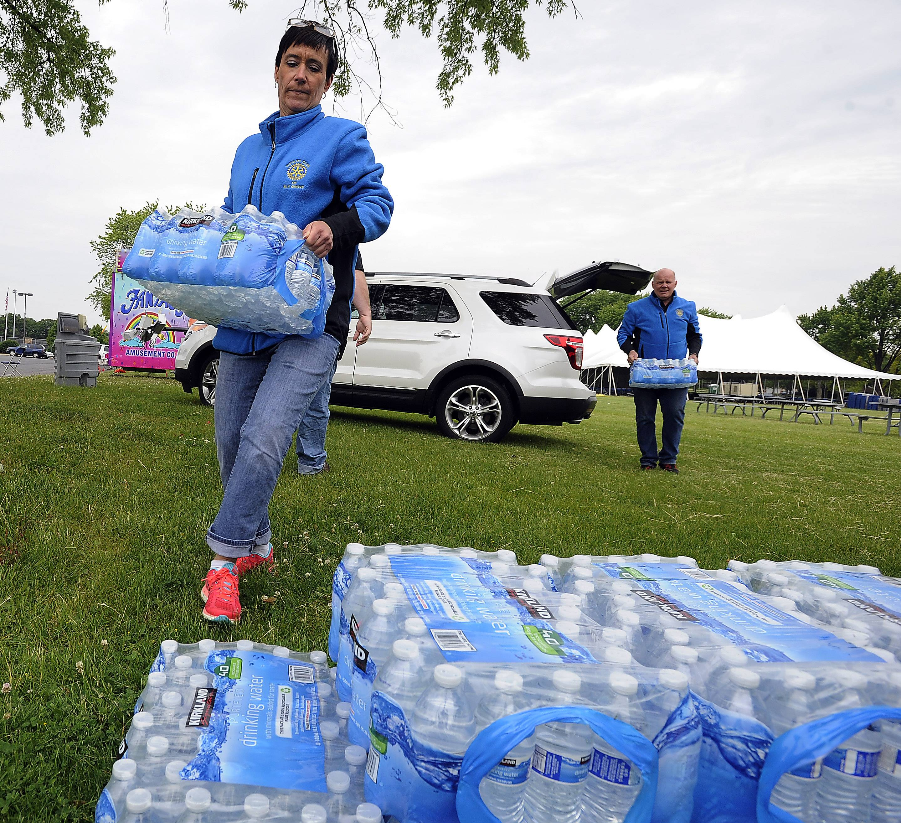 Donna Bartoli, board member, and Bill Marston, Chairman of the Elk Grove Rotary, haul water to the tents as they prepare for the 2014 RotaryFest carnival in Lions Park in Elk Grove Village.