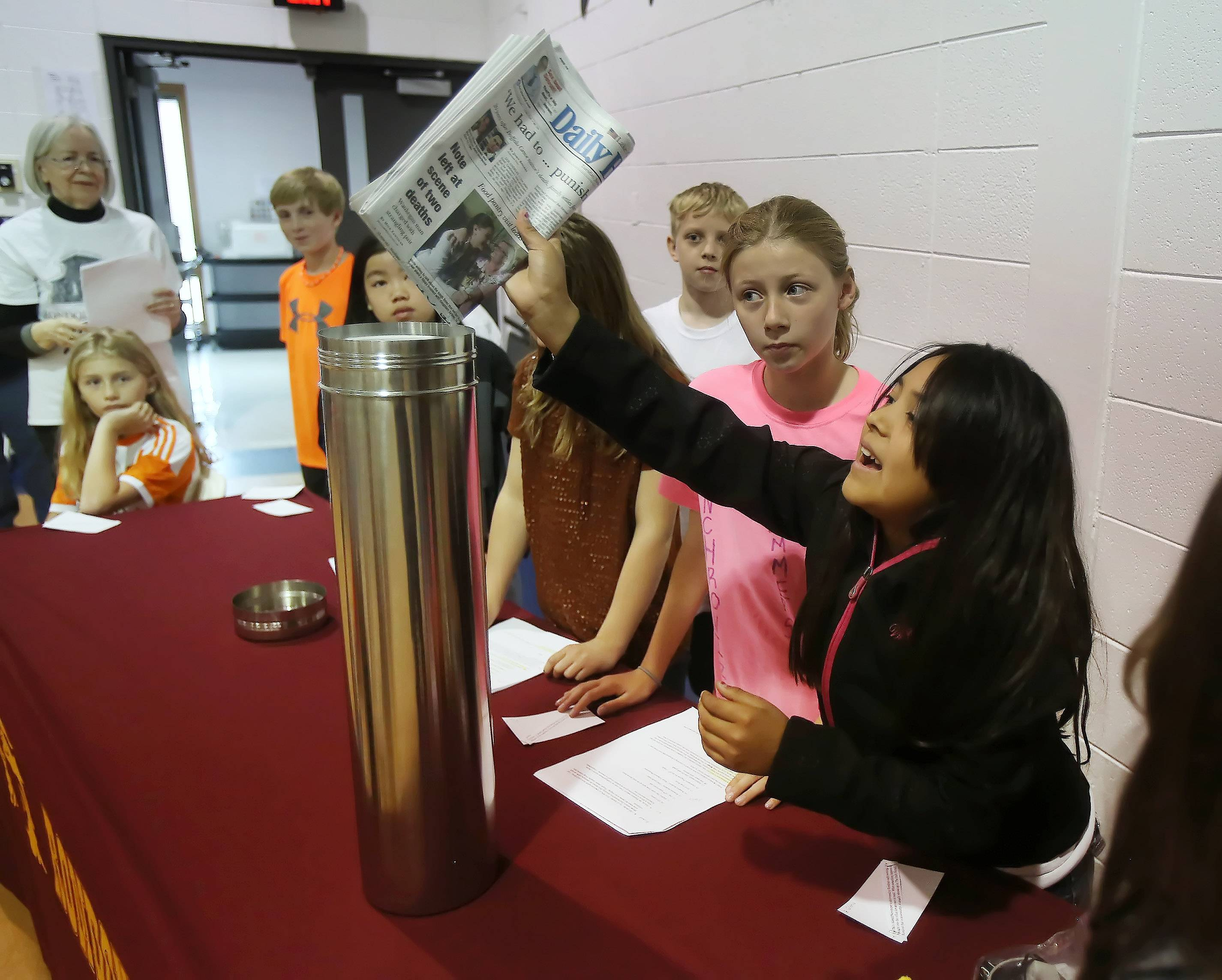 Fourth grader Gloria Barbosa-Gomez places a newspaper in a time capsule during the Rondout Time Capsule Ceremony on the last day of school as part of Rondout School District's Sesquicentennial Celebration. Some of the items inside the capsule included a flash drive, a cellphone, a newspaper, Post-it's, a Toobaloo and the school mascot Falcon toy.