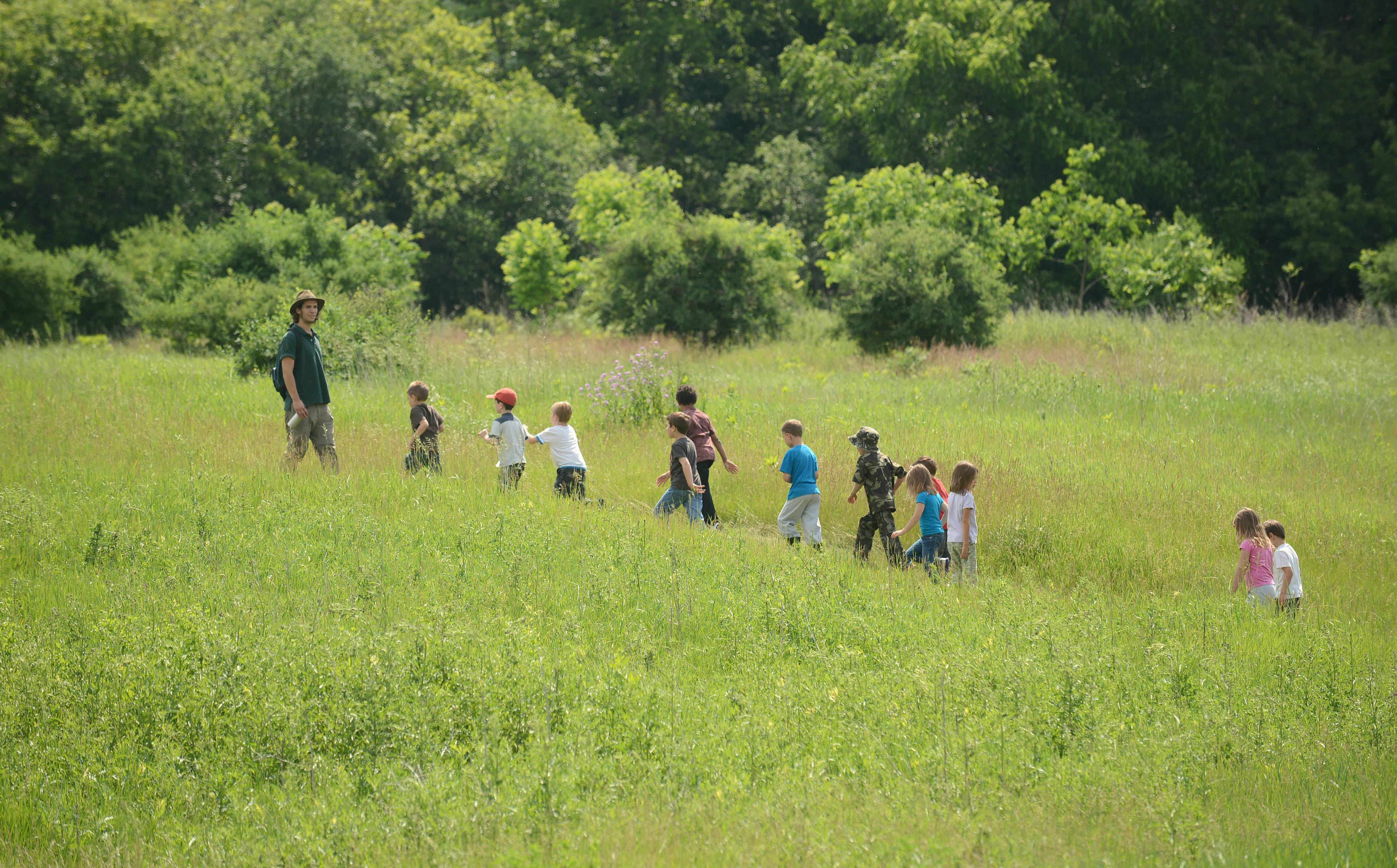 "Kane County Forest Preserve naturalist Josh Libman, far left, leads a group of first and second graders on a hike into the woods to learn how to build a natural fort at LeRoy Oakes Forest Preserve in St. Charles on Thursday. 20 youngsters attended the ""Week in the Woods"" camp at the preserve, studying different aspects of nature each day of the week. Daily themes included mammals, birds, insects and ""Humans in Nature."" Kids learned the importance of humans respecting the environment, what they can recycle and compost, making a craft from natural elements and even building a nature fort for protection."