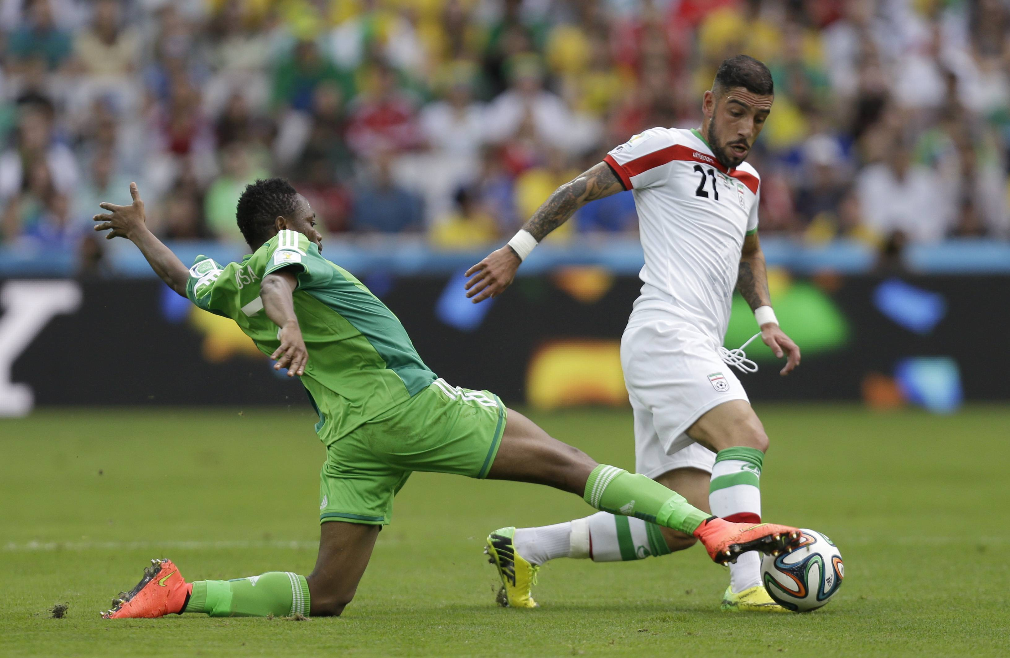 Nigeria's Ahmed Musa, left, challenges Iran's Ashkan Dejagah during the group F World Cup soccer match between Iran and Nigeria at the Arena da Baixada in Curitiba, Brazil, Monday.