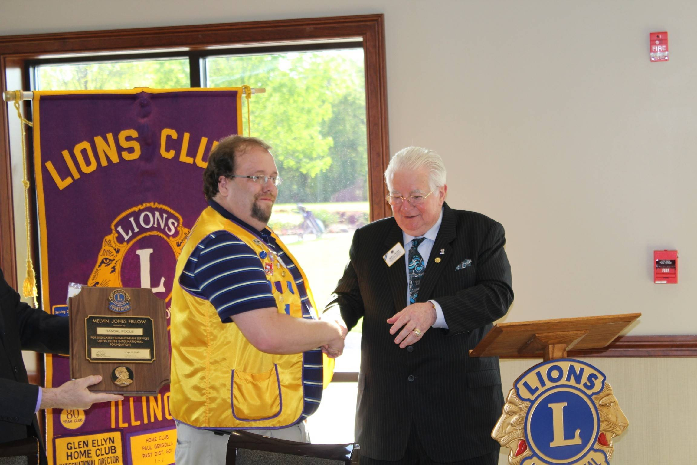 Lions International President Barry J. Palmer, right, presents Glen Ellyn Lion Randy Poole with the Melvin Jones Fellowship Award, the highest form of recognition for an individual who has given exemplary service to his club and community.