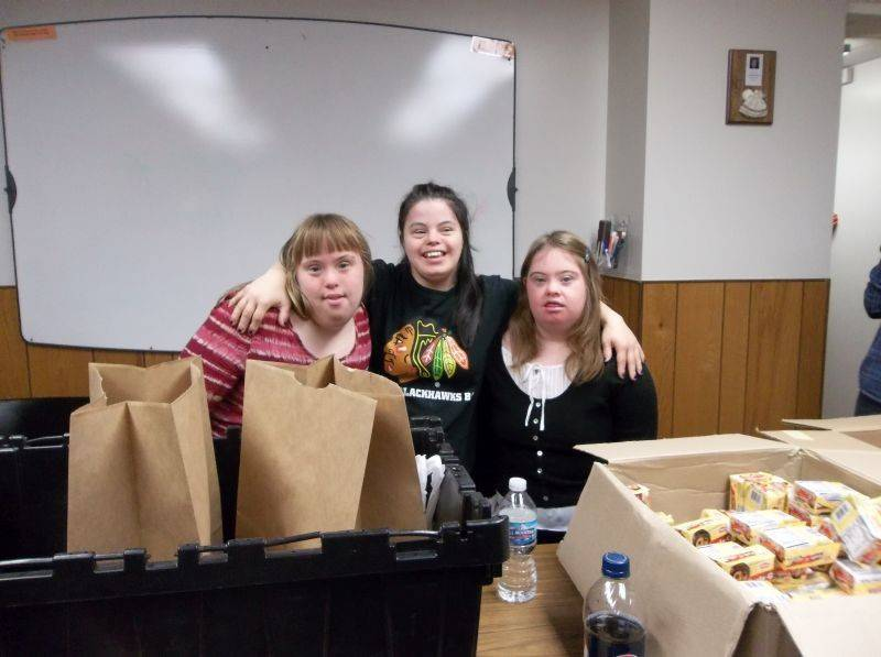 From left, Emma Scheid, Christina Macchitelli and Katrina Daly, participants in NEDSRA's TREC program, take a break from filling bags of food for DuPage County families in need.