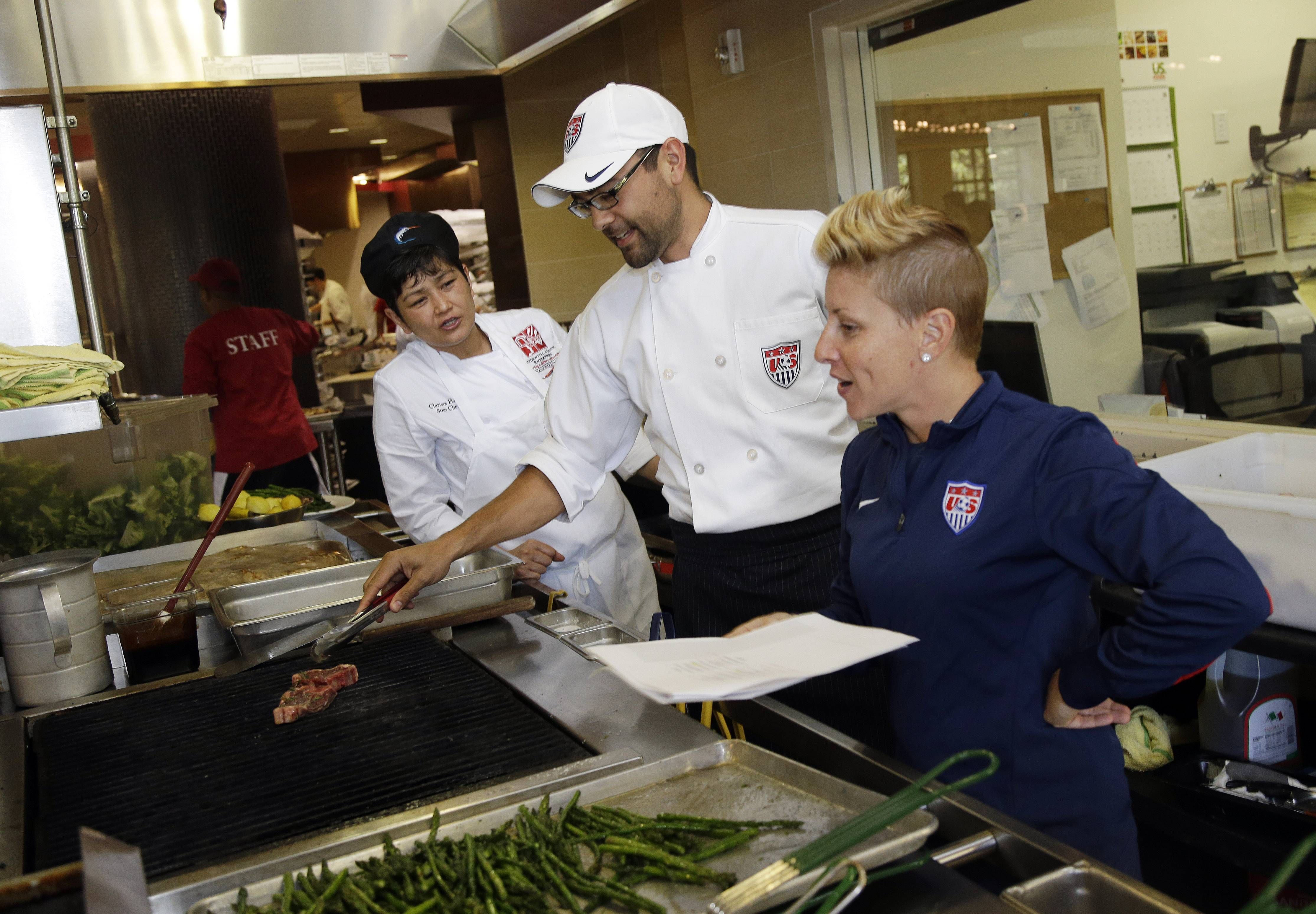 U.S. soccer dietitian Danielle LaFata, right, goes over the lunch menu with the team's chef Bryson Billapando, center, and Stanford chef Clarissa Flores during the team's training in Stanford, Calif., in preparation for the World Cup soccer tournament in Brazil.