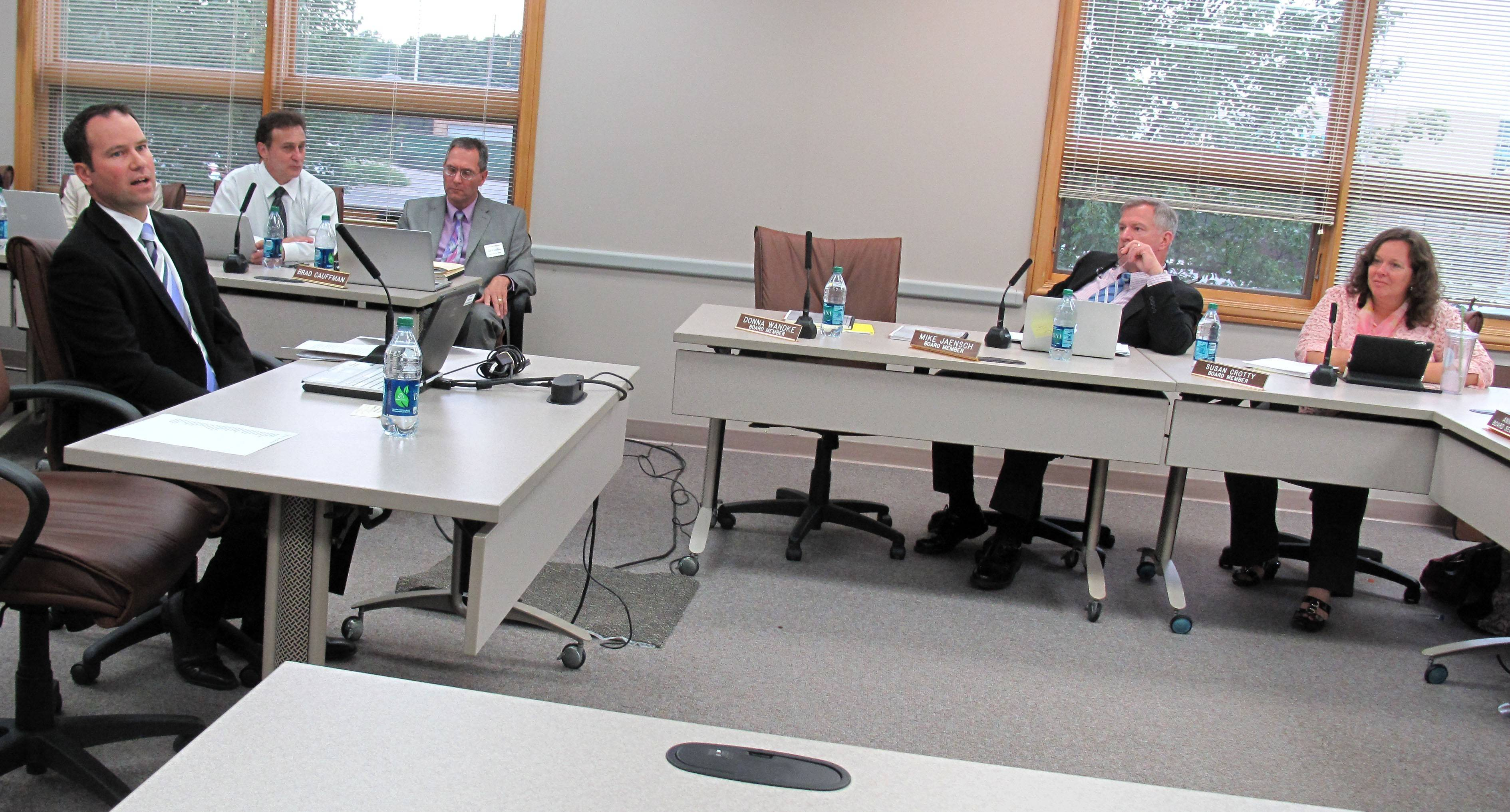 Ken Banas of Lisle shares concerns Monday night with Naperville Unit District 203 board members including Mike Jaench and Susan Crotty, right, about the possible lease of cell towers at Kennedy and Lincoln junior high schools.