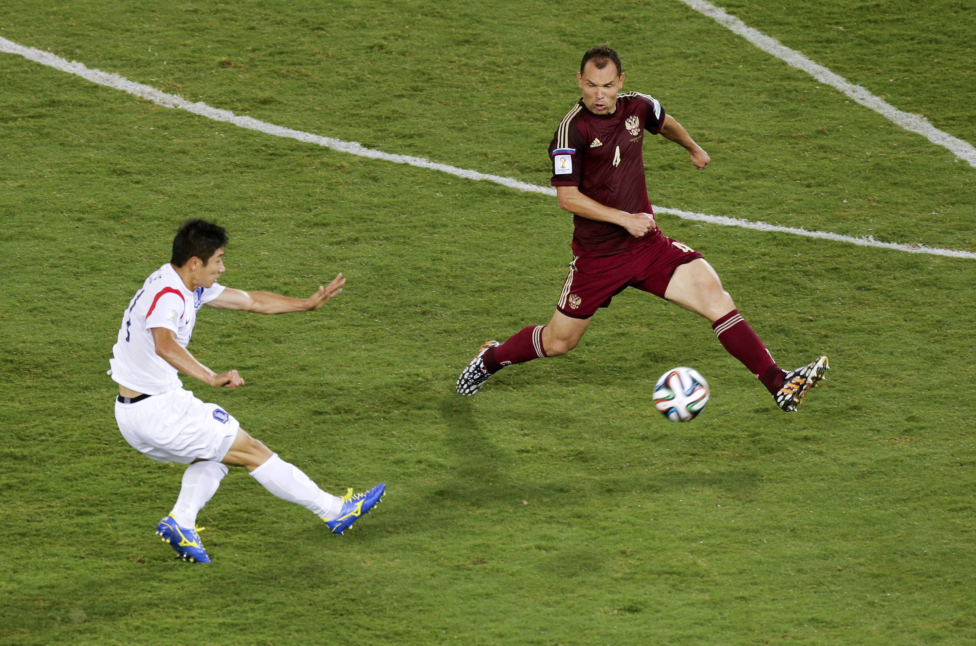 South Korea's Lee Keun-ho, left, scores the opening goal past Russia's Sergei Ignashevich (4) during the group H World Cup soccer match between Russia and South Korea at the Arena Pantanal in Cuiaba, Brazil, Tuesday, June 17, 2014. (AP Photo/Thanassis Stavrakis)