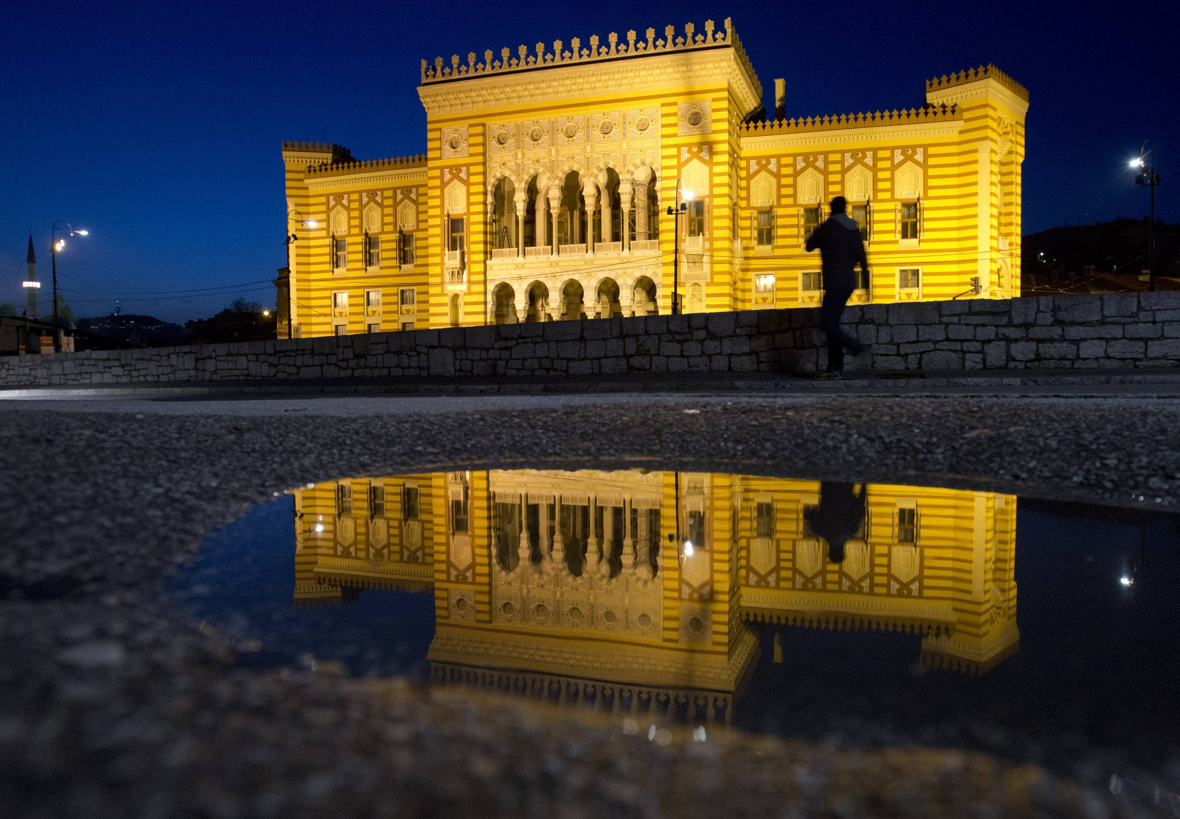 The City Hall is reflected in a puddle in Sarajevo, Bosnia-Herzegovina. The city will host a number events around the Centenary of World War I, including a conference of historians and a concert.