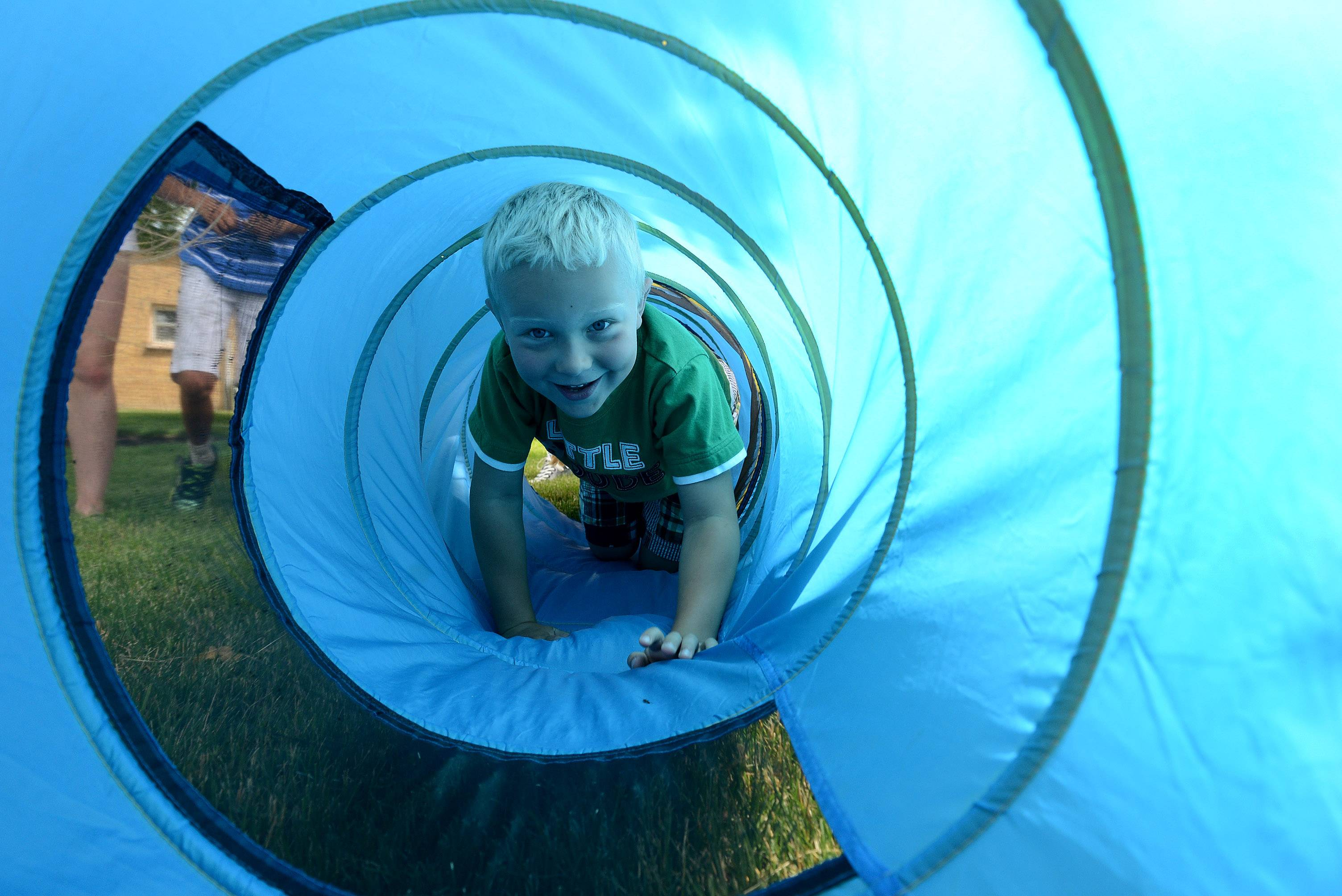 Hunter Kleiboer, 6, Lake Villa, makes his way through the tunnel on the obstacle course during the 4-H Health Rocks Summer Day Camp at the University of Illinois Extension in Grayslake for 5- to 7-year-olds.