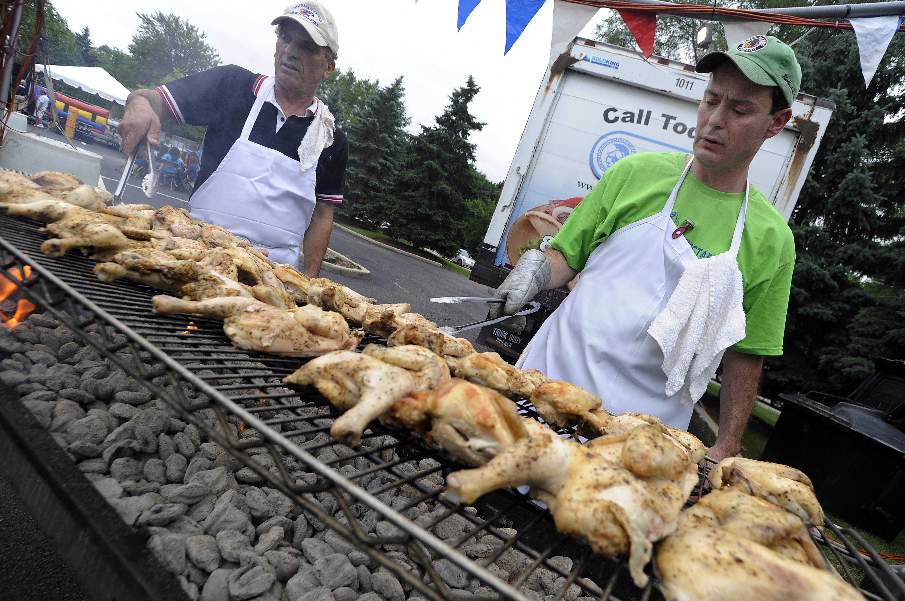 Peter Phillips of Schaumburg (right) along with John Giannopoulos of Hanover Park cook up St. Nectarios of Palatine's famous chicken during a recent Greek Fest celebration. The annual festival returns to the Palatine church this weekend, featuring the best in Greek food, culture and music.