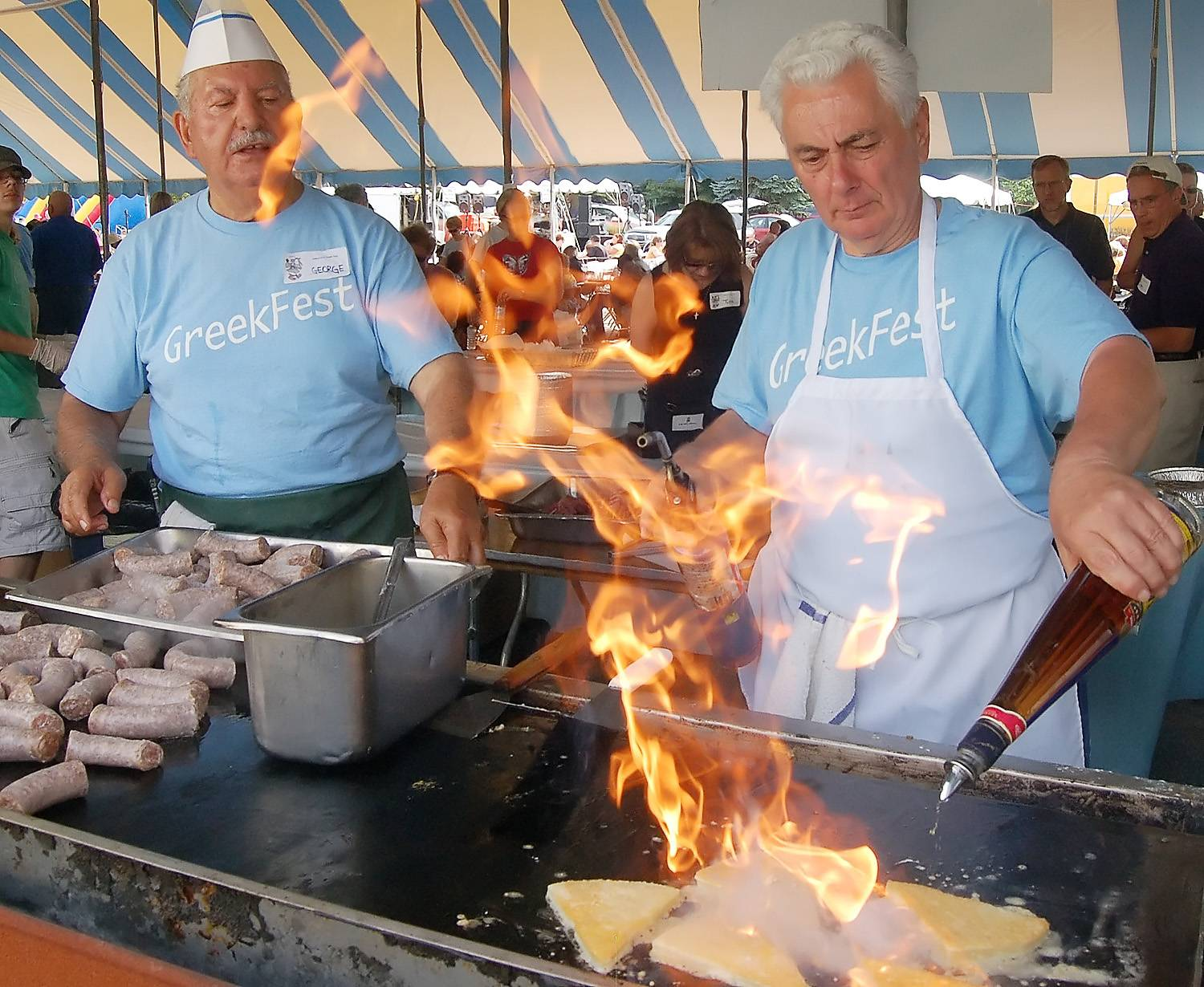 John Mathias puts the final touches on the Kelografeda flaming cheese while George Glitsohis cooks Greek sausage during a recent Greek Fest at St. Nectarios Church in Palatine. The three-day annual festival returns this weekend, featuring the best in Greek food, culture and music.