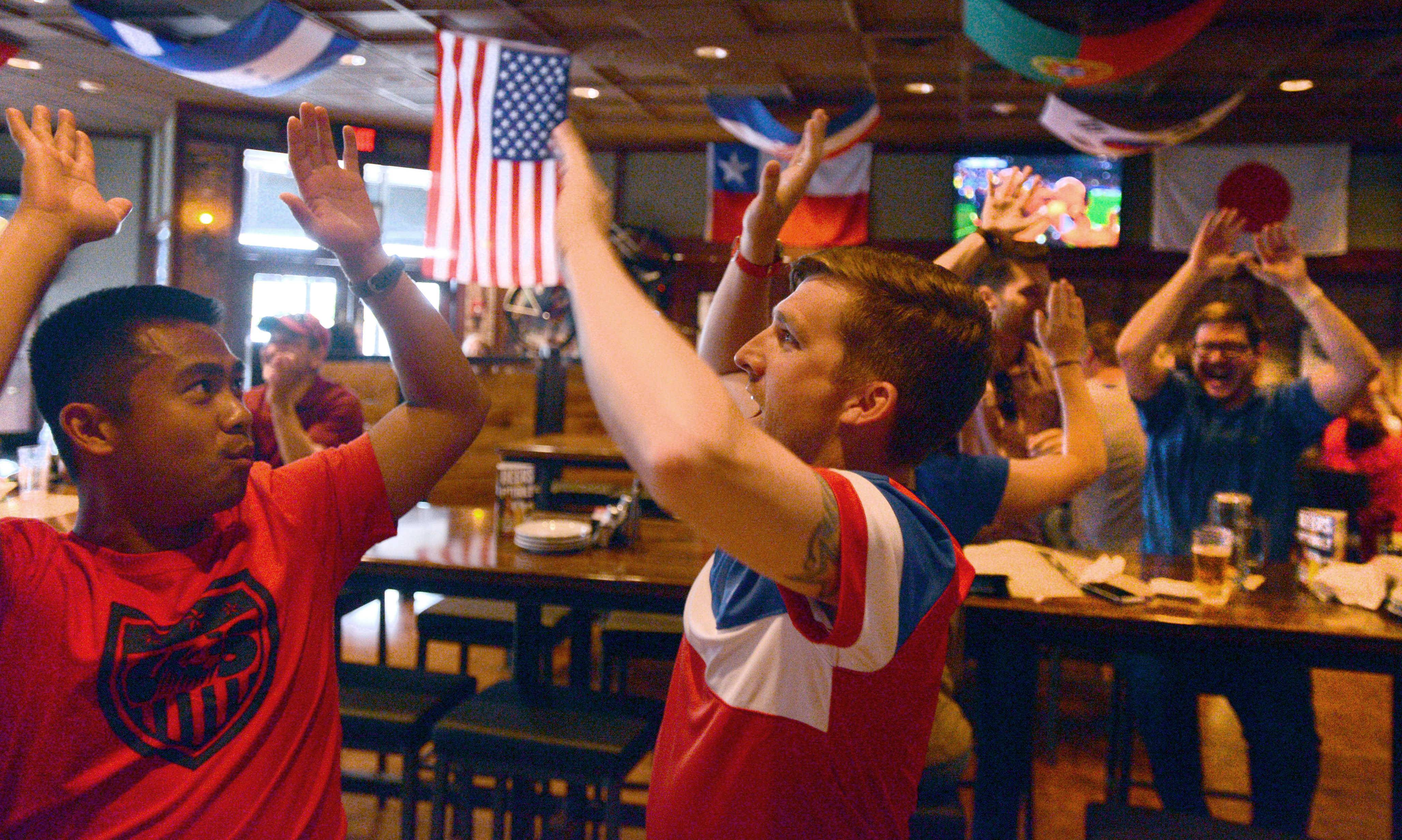 Jonathan Acosta, left, of Addison, and Steve Jenkins of Hoffman Estates have something to be happy about at the conclusion of the United States World Cup soccer game against Ghana on Monday night at the Fox & Hound Sports Tavern in Schaumburg.