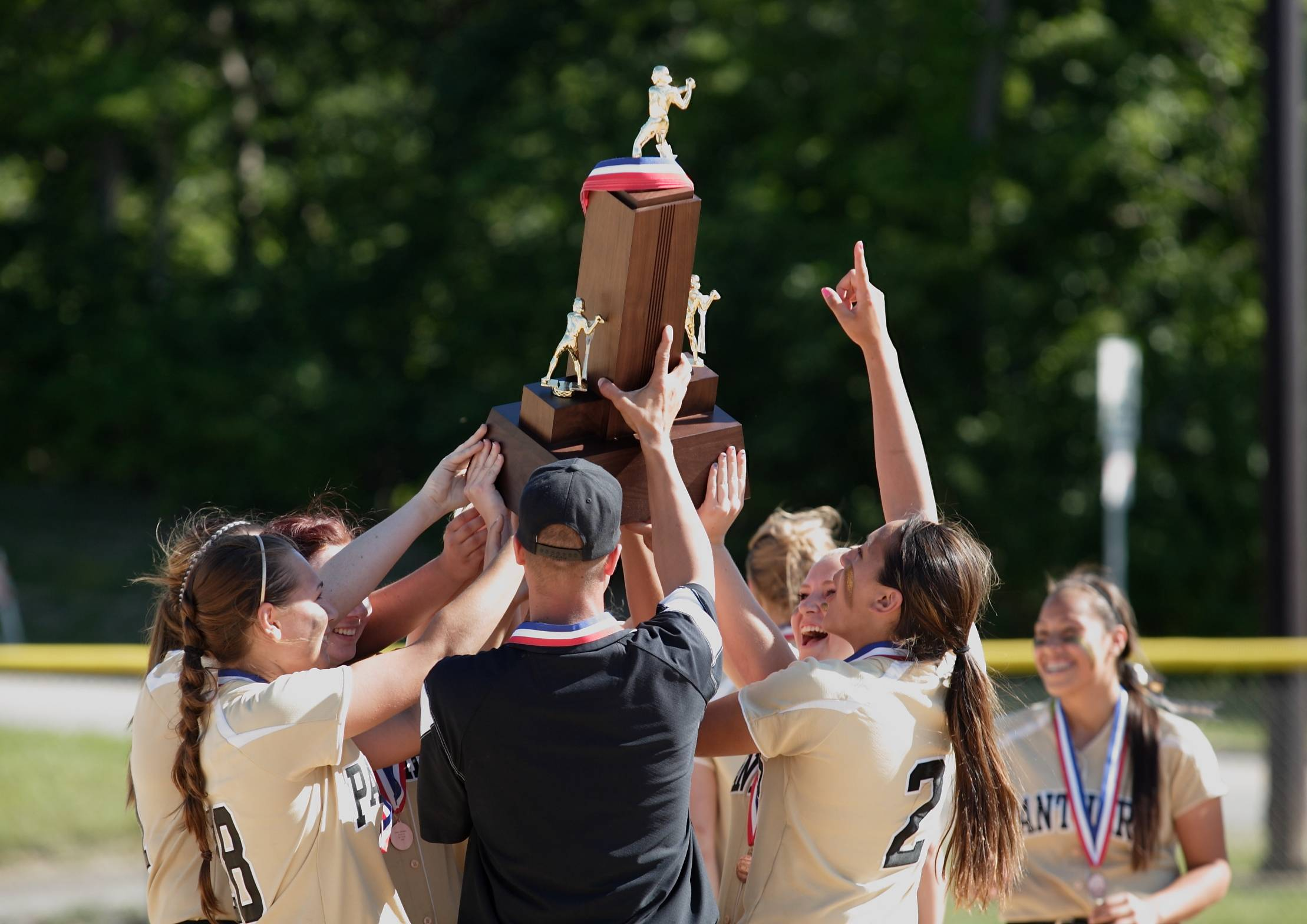 Members of the Glenbard North softball team hoist their third-place trophy after their IHSA Class 4A third-place game on Saturday. Glenbard North defeated Lincoln-Way East, 6-0.