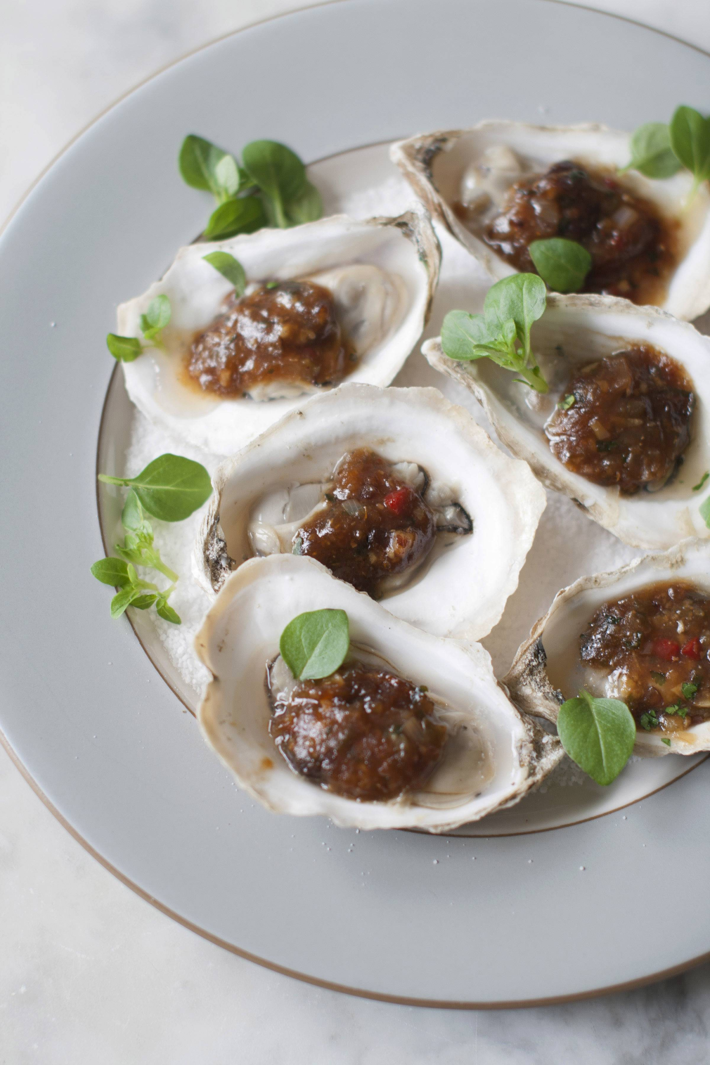 Turn a raw-bar treat until a summertime favorite with a recipe for grilled oysters with fermented black beans and chili garlic inspired by chefs at the South Beach Wine and Food Festival in Miami Beach, Fla.