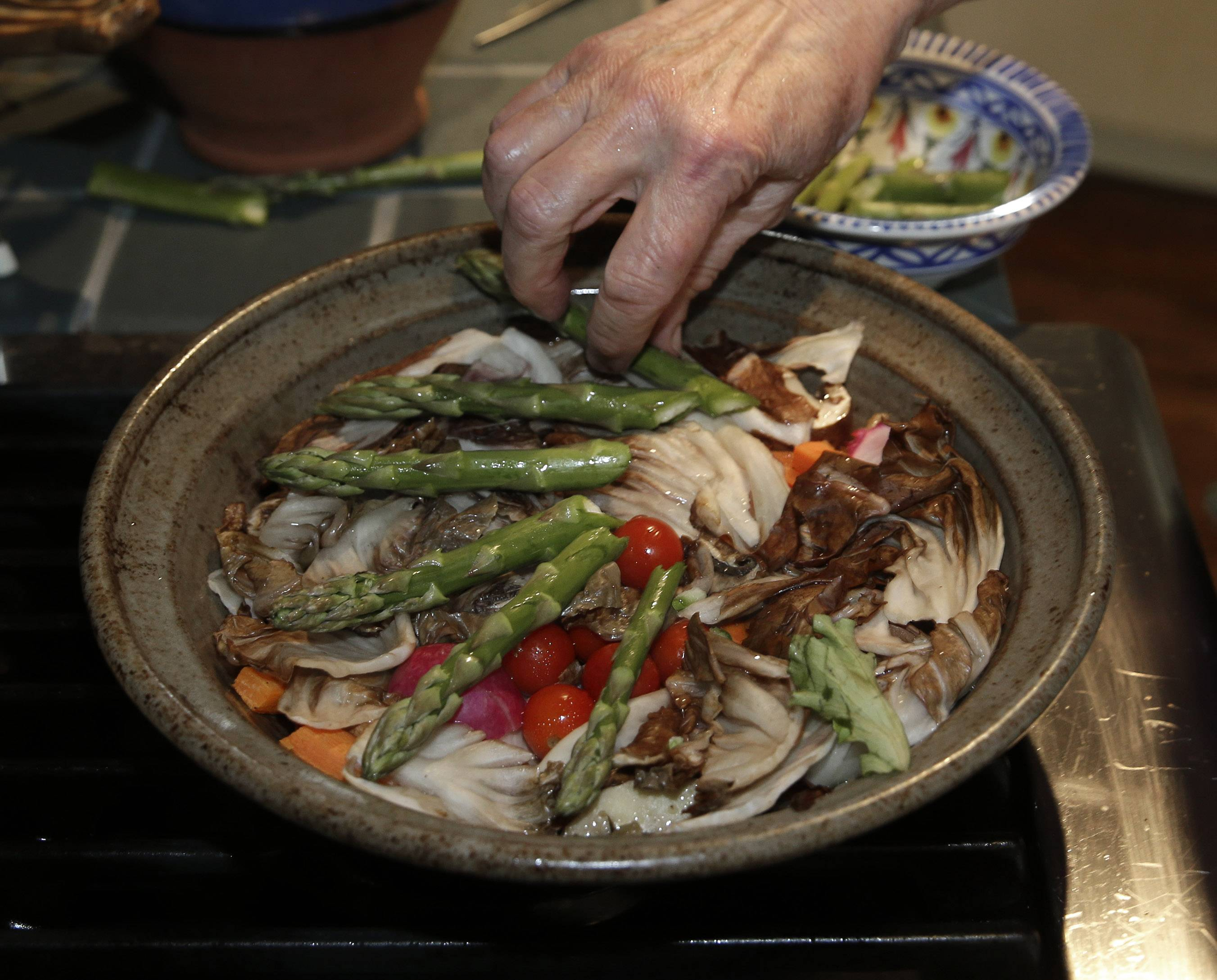 Cookbook author Paula Wolfert places asparagus in with other vegetables to slow cook for lunch at her home in Sonoma, Calif. Wolfert spent more than 50 years researching and writing about food. Now she's enlisting food as an ally in a fight to stay mentally sharp.