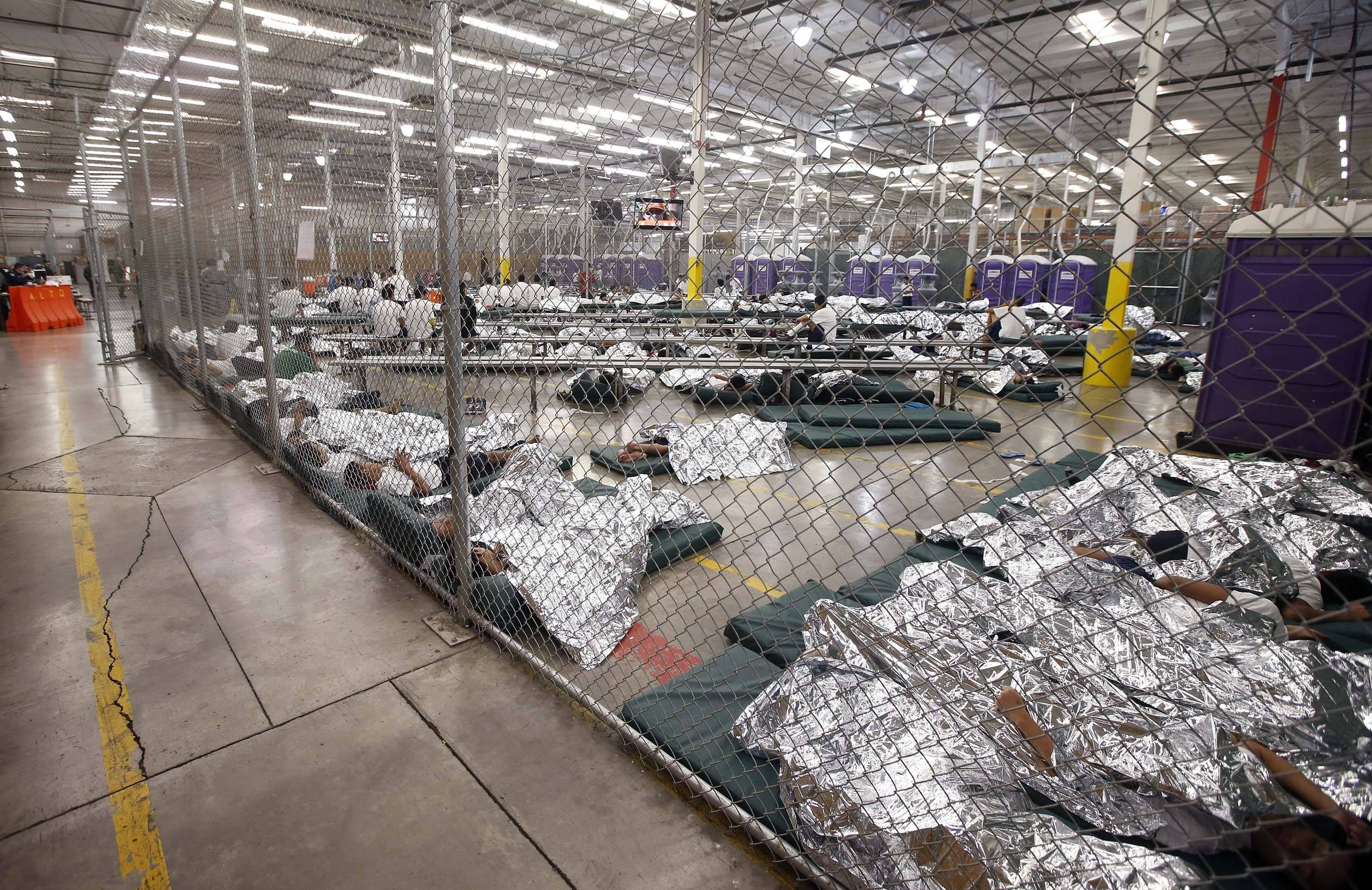 Detainees sleep and watch television in a holding cell Wednesday where hundreds of mostly Central American immigrant children are being processed and held at the U.S. Customs and Border Protection Nogales Placement Center in Nogales, Ariz. CPB provided media tours Wednesday of two locations in Brownsville, Texas, and Nogales, that have been central to processing the more than 47,000 unaccompanied children who have entered the country illegally since Oct. 1.