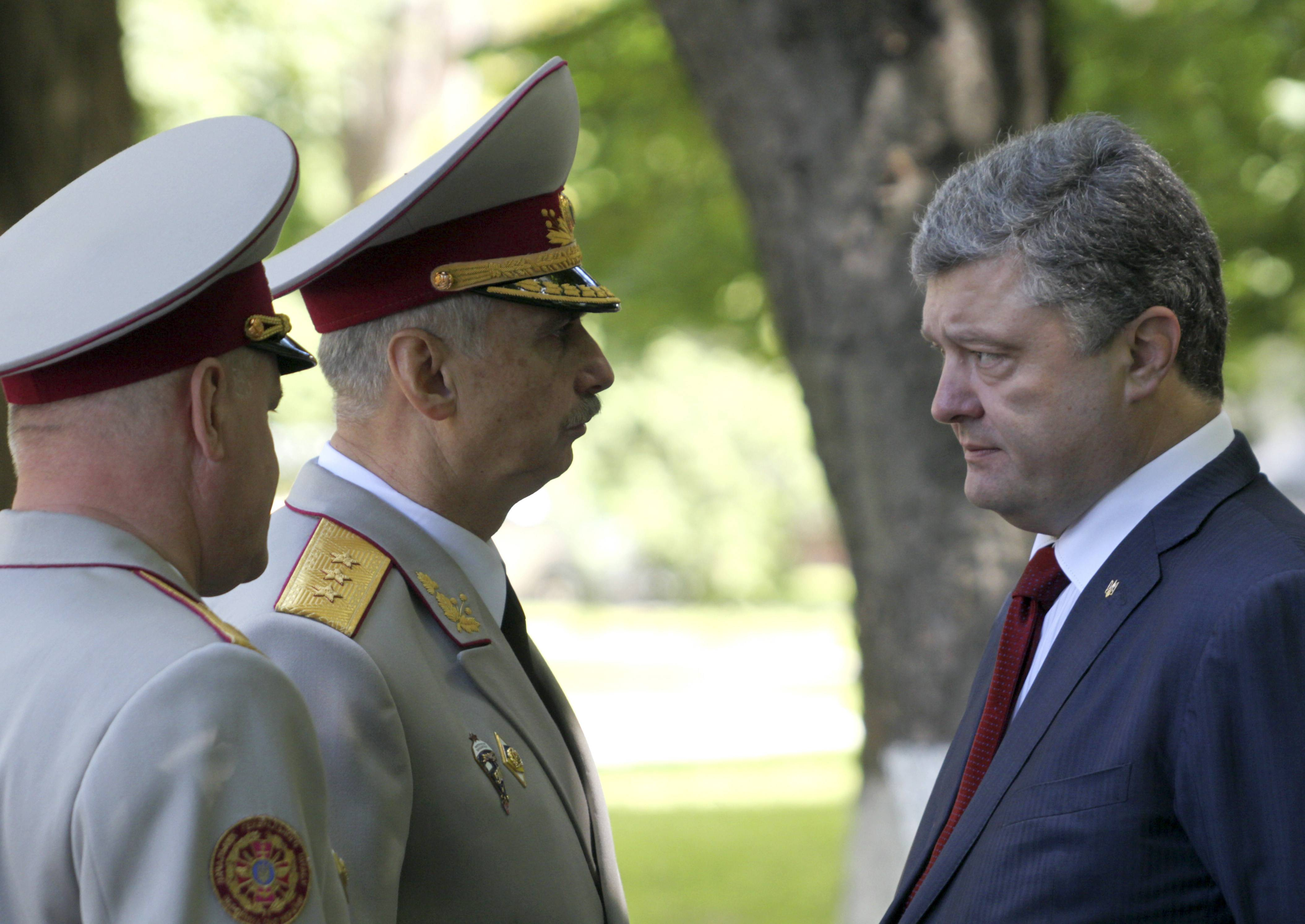 Ukrainian President Petro Poroshenko, right, meets Wednesday with acting Ukrainian Defense Minister Mykhailo Koval, center, in Kiev, Ukraine. Ukraine's president said Wednesday that government forces will unilaterally cease-fire to allow pro-Russian separatists in the east of the country a chance to lay down weapons or leave the country, a potential major development to bring peace to the country.