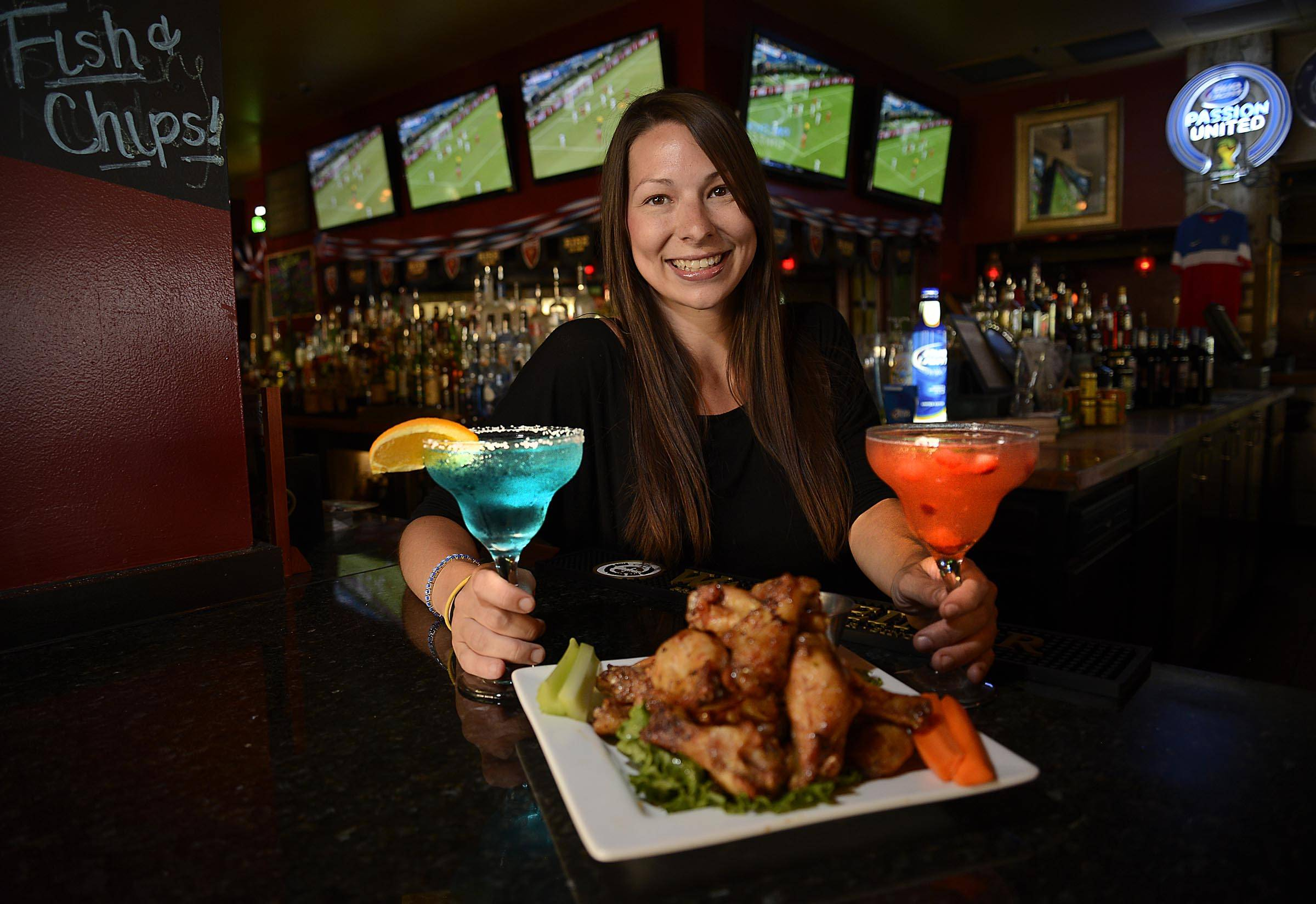 Nicollette Parra serves up wings and new summer martinis Red Headed Sunset and Deep Blue Sea at the Claddagh Irish Pub in Geneva during the World Cup.