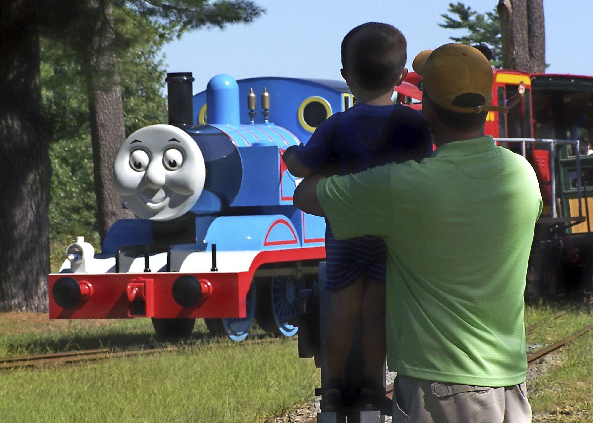 A father and son watch Thomas the Tank Engine roll down the track at an annual Day Out with Thomas event at the Edaville USA theme park in Carver, Mass. Groundbreaking for the first permanent Thomas Land in the U.S. is set for July 2014 at Edaville USA, and is expected to be open for business in the summer of 2015.
