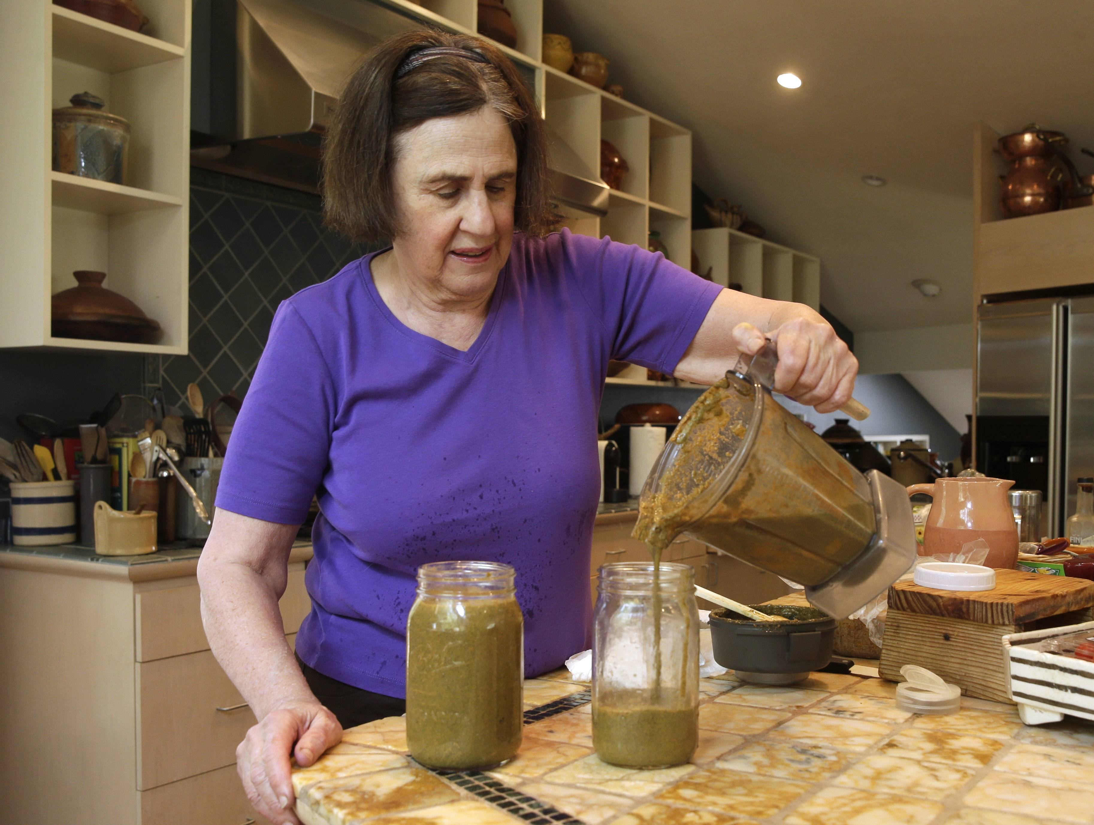 Paula Wolfert pours a smoothie mix into jars for storage at her home in Sonoma, Calif.