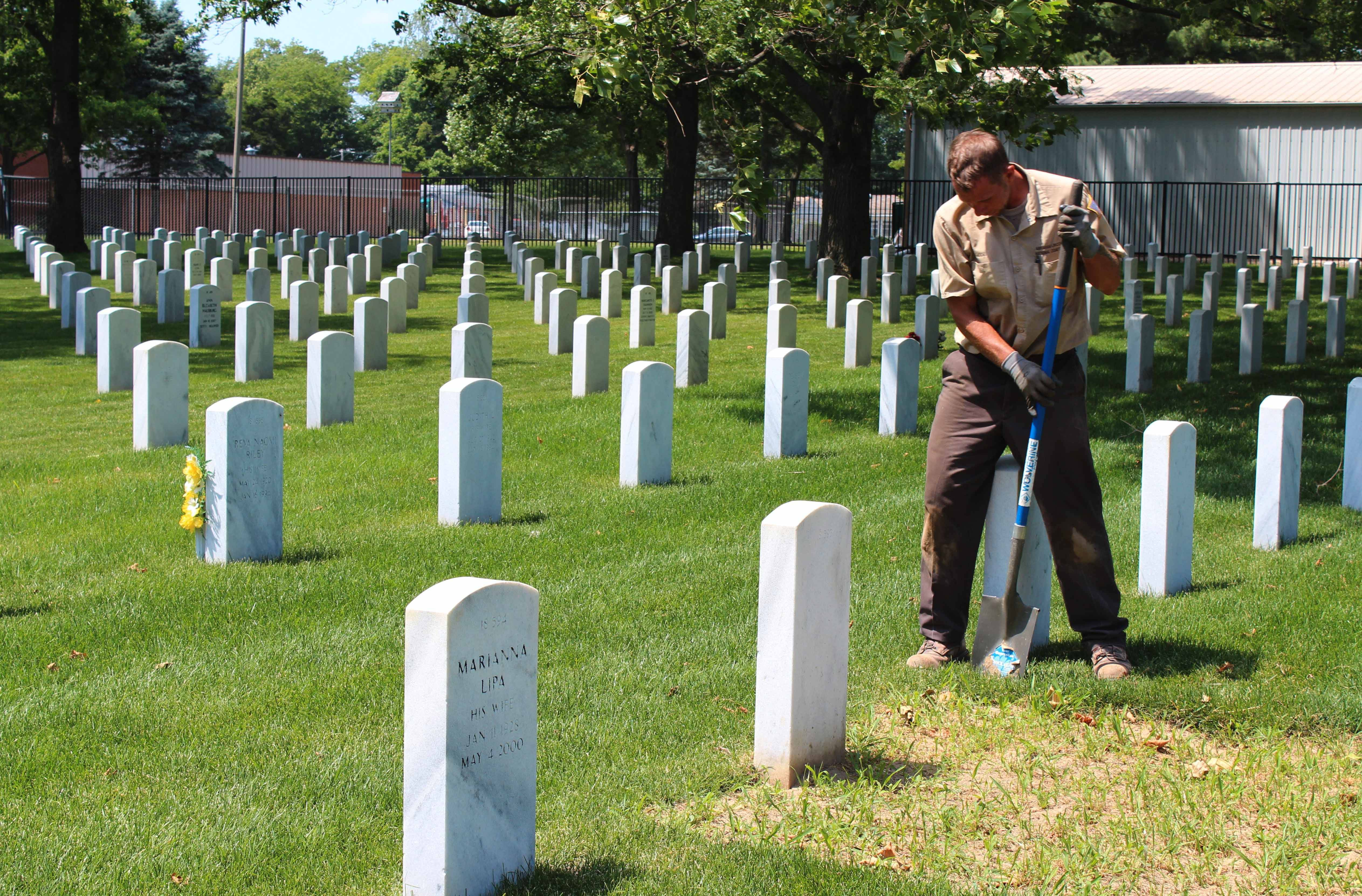 Joe Curran works on sod Tuesday in the Danville National Cemetery in Danville, Ill. Curran was transferred temporarily this week from Abraham Lincoln National Cemetery near Joliet to help the Danville cemetery, which has had staff reductions.