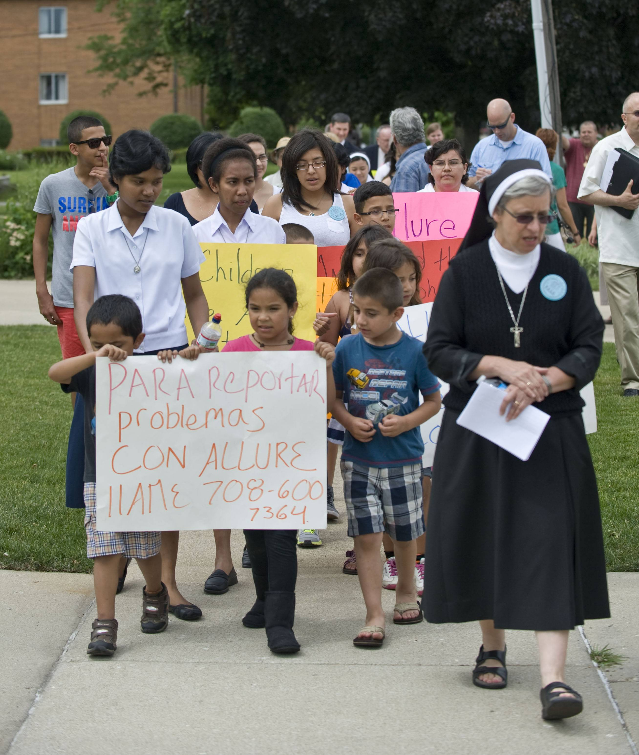 At right, sister Noemia Silva of the Missionary Sisters of Saint Charles Borromeo Scalabrinians walks with children and neighbors Wednesday to Club Allure Chicago, a strip club, to protest its proximity to their convent.