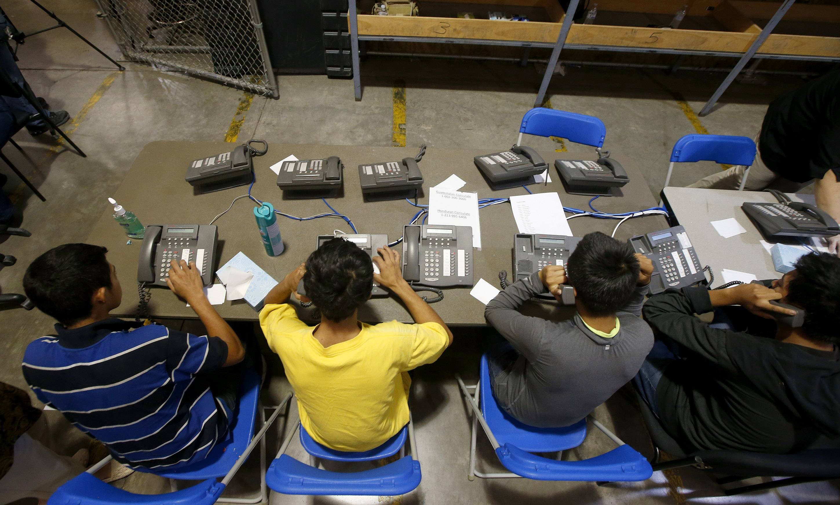 A few boys try to make calls Wednesday as they are joined by hundreds of mostly Central American immigrant children that are being processed and held at the U.S. Customs and Border Protection Nogales Placement Center in Nogales, Ariz.