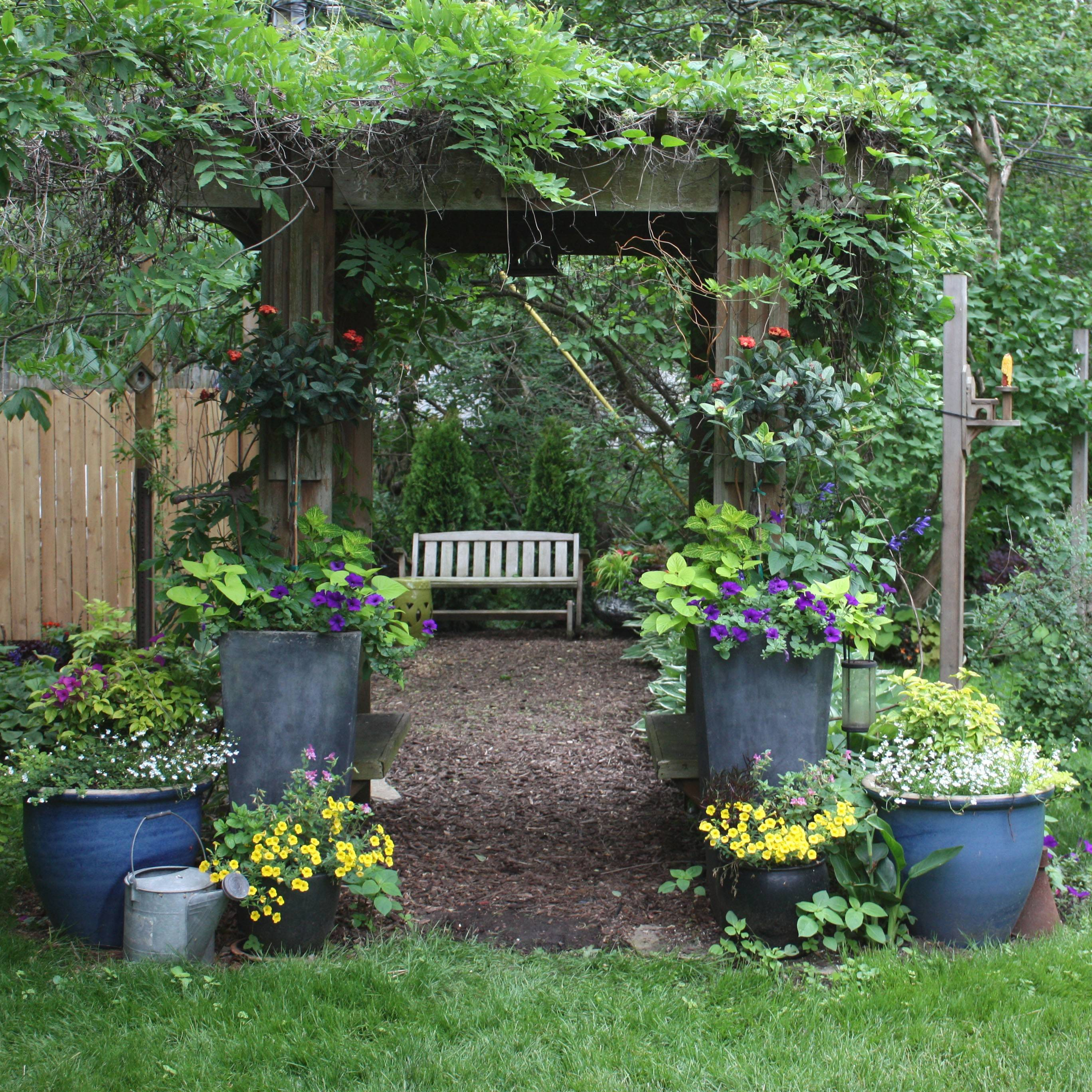 The attractive arbor that Tim Stewart built for their garden encloses a parallel pair of seats. Across the top twine autumn mist clematis and purple wisteria as pots of colorful annuals adorn the entrance.