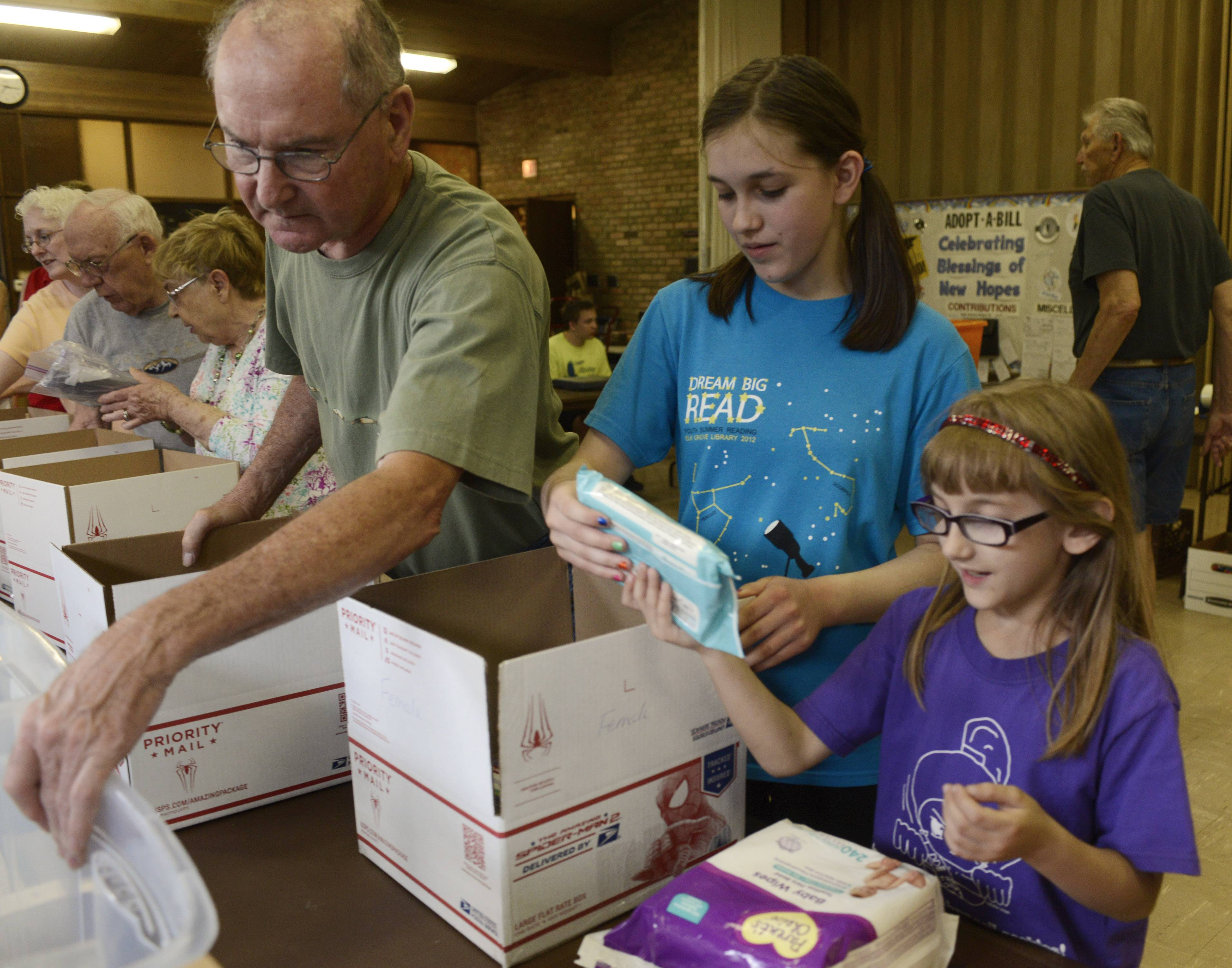 "Bob Pruyn, left, of Elk Grove Village works alongside Carissa Lehning, 14, of Elk Grove Village and her sister, Ashley, 8, as they load boxes of personal items, food and candy destined for U.S. soldiers during an event Tuesday at the Lutheran Church of the Holy Spirit. ""I remember getting care packages when I was in Vietnam,"" Pruyn said. ""This is my payback."""