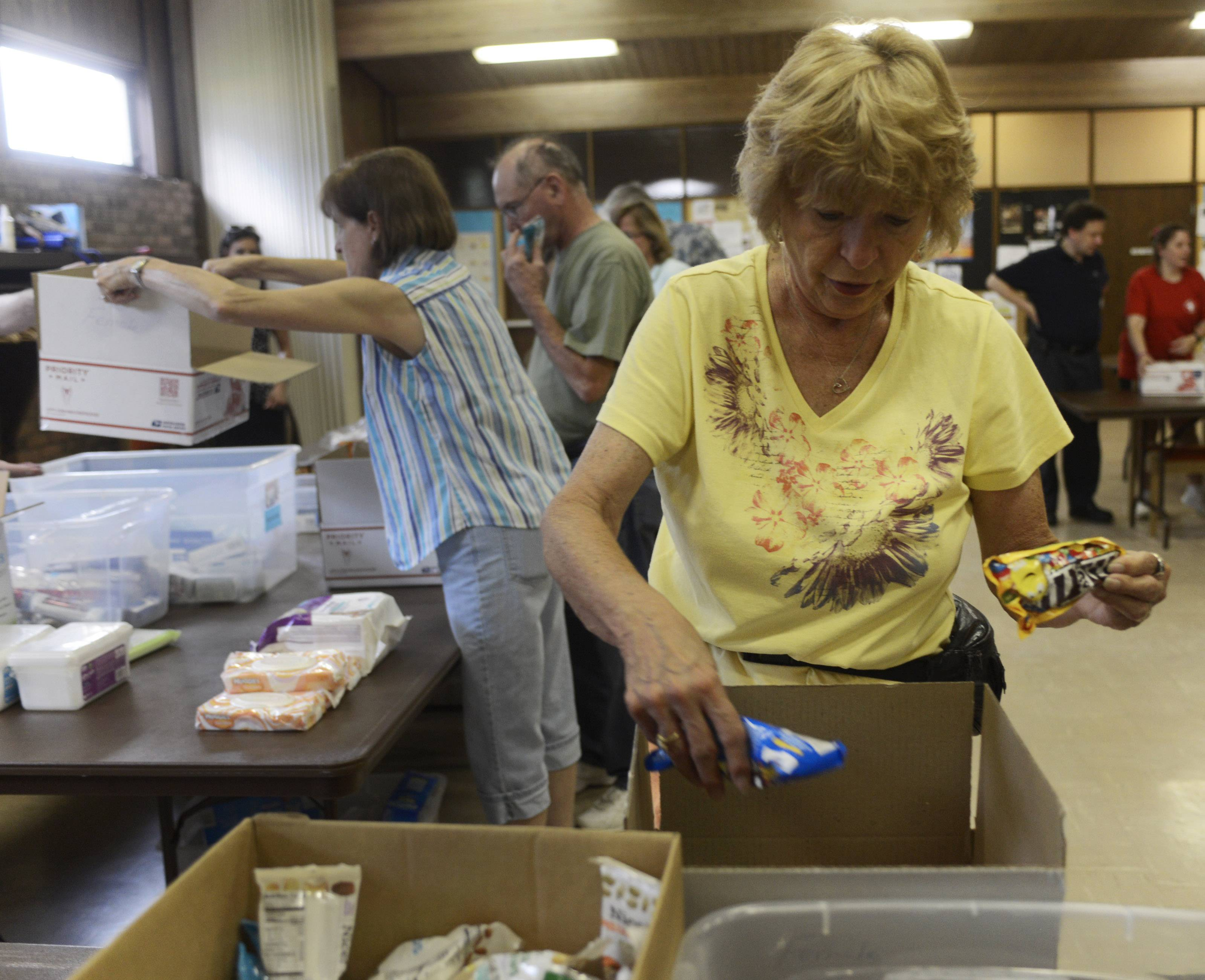 Karen Schichi of Elk Grove Village helps pack boxes loaded with personal items, food and candy for U.S. soldiers serving overseas during a Packages 4 Patriots event Tuesday night at the Lutheran Church of the Holy Spirit in Elk Grove Village.