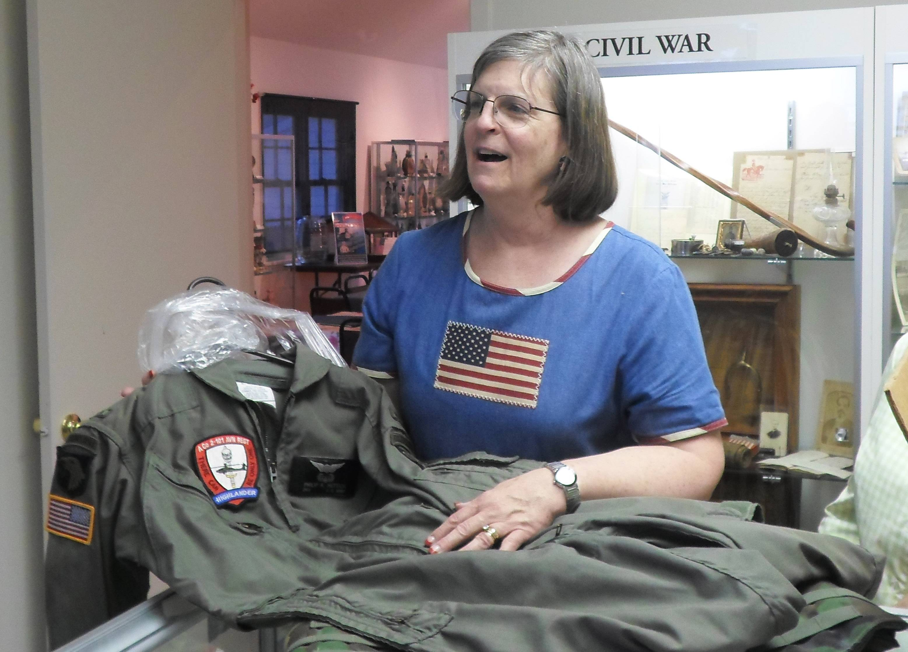 Lakes Region Historical Society board member Ainsley Wonderling talks about a flight suit donated to the organization.