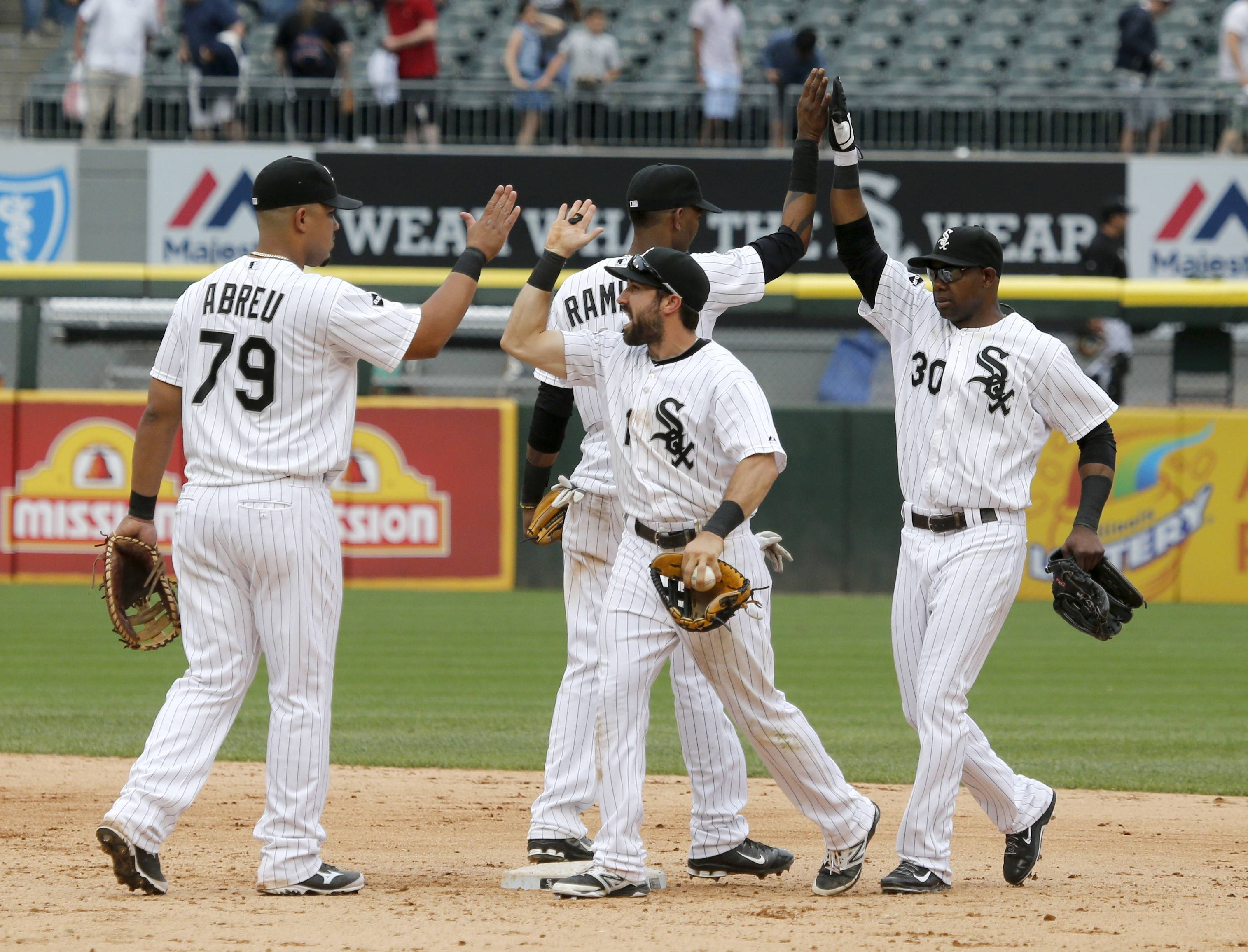 Celebrating the White sox' win over the Giants, from left, are Jose Abreu, Alexei Ramirez, Adam Eaton and Alejandro De Aza on Wednesday at U.S. Cellular Field.