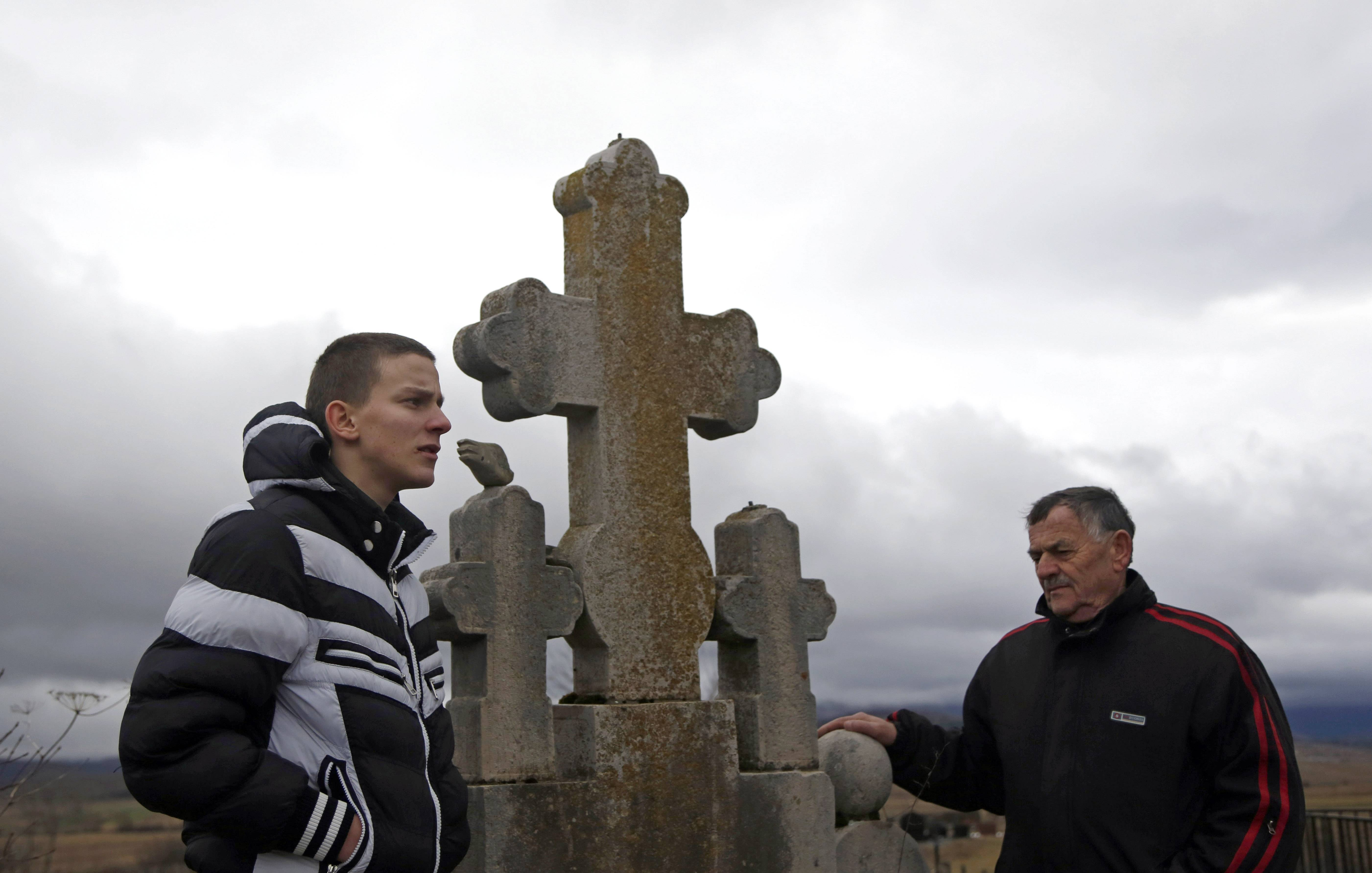Gavrilo Princip's relatives, Nikola Princip, right, and his grandson, Novak Princip, 16, pay their respects at the Princip family plot in a cemetery in the village of Obljaj, near Bosansko Grahovo, Bosnia. A century later, Gavrilo Princip still provokes controversy from beyond the grave as his legacy has been molded time and again to meet political agendas in the Balkans, still a patchwork of ethnic and religious rivalries.