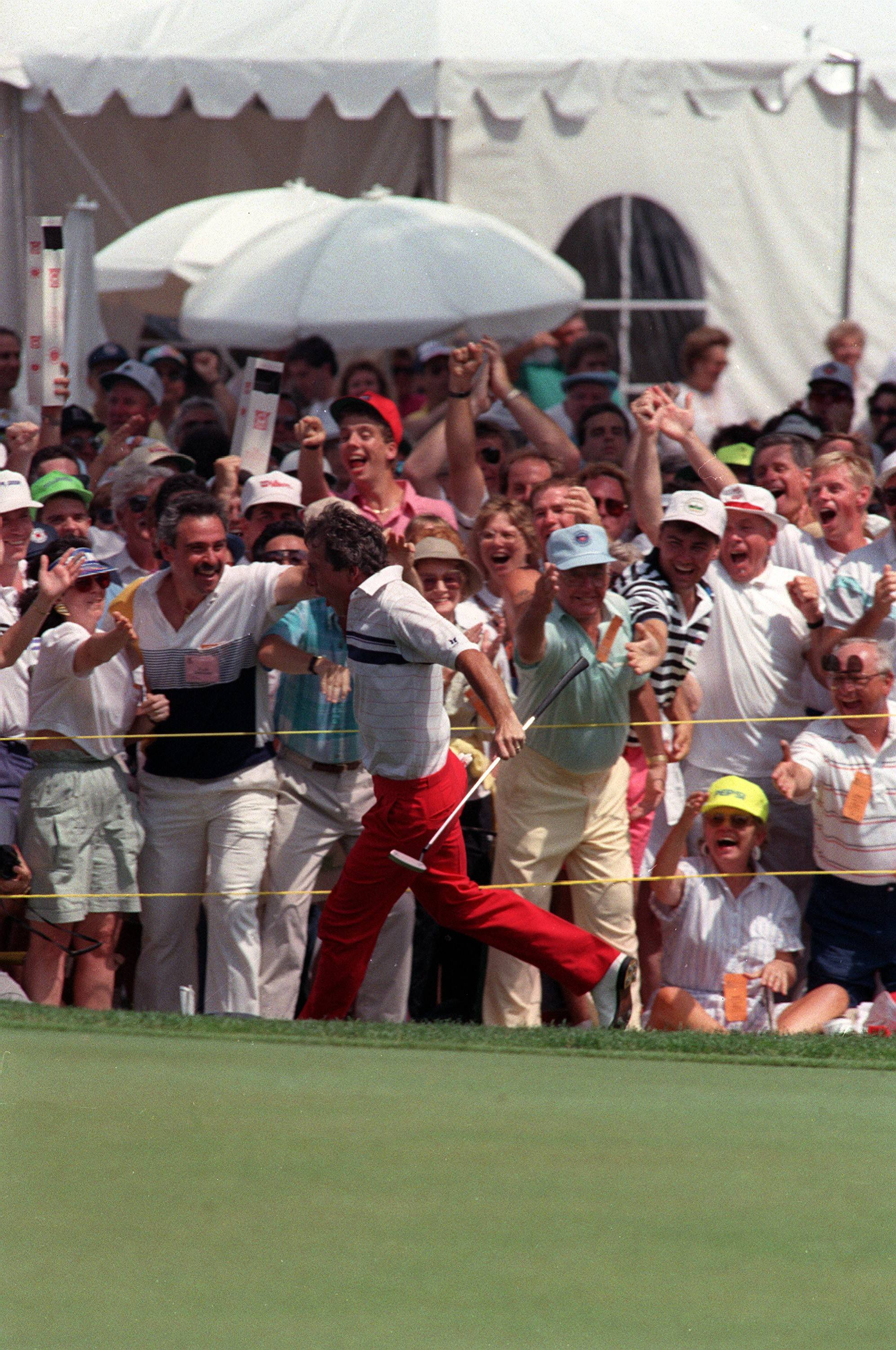 Two time U.S. Open winner Hale Irwin gets a round of high-fives from the fans surrounding the 18th green after sinking a 60-foot putt during the U.S. Open at Medinah Country Club in Medinah, Ill., Sunday, June 17, 1990. The play put Irwin in the clubhouse at 8-under for the tournament. Irwin won the championship in playoffs with a score of 280. (AP photo/Charles Bennett)