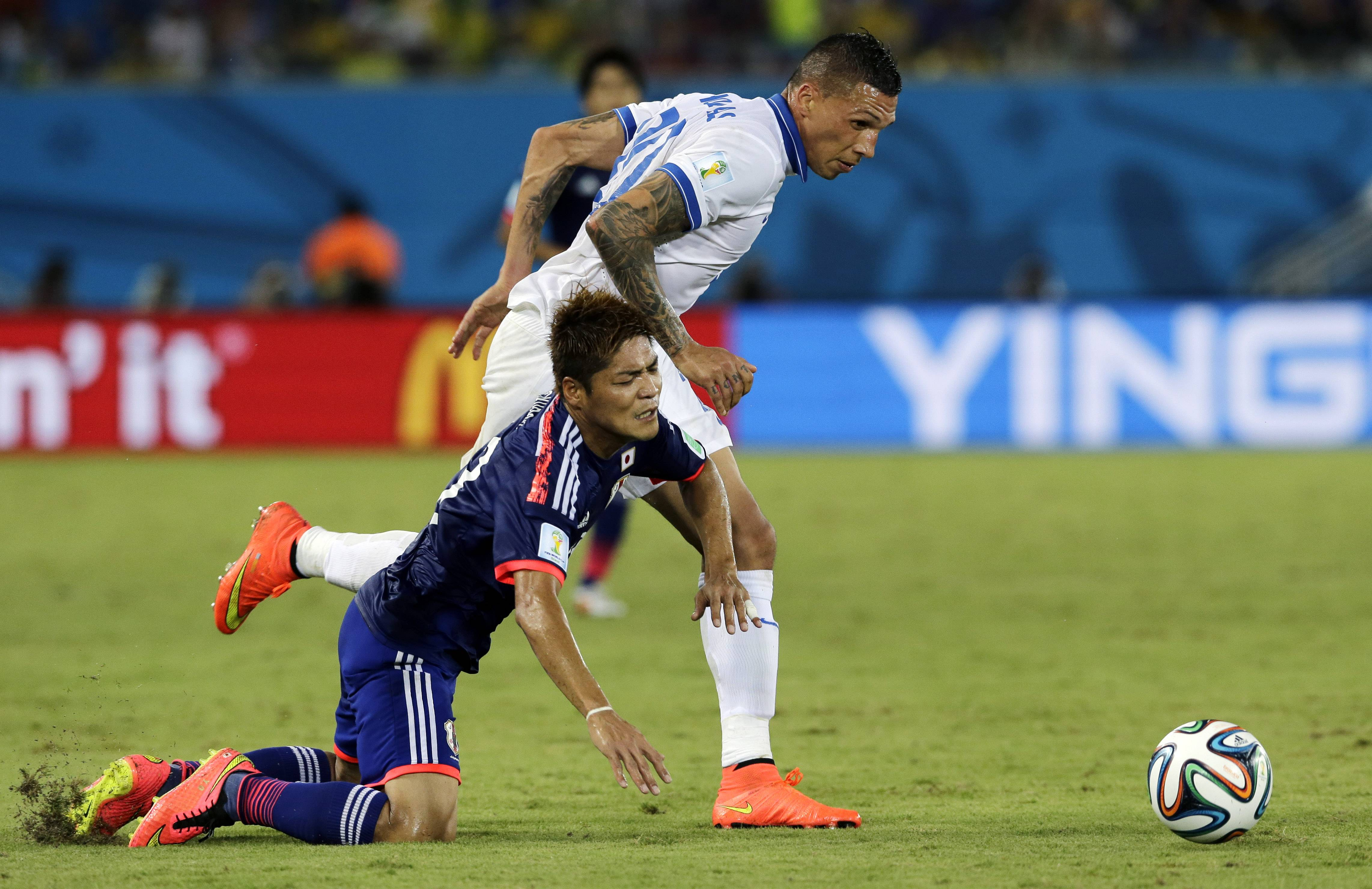 Greece's Jose Holebas, right, pulls down Japan's Yoshito Okubo while chasing the ball during the group C World Cup soccer match between Japan and Greece at the Arena das Dunas in Natal, Brazil, Thursday, June 19, 2014. (AP Photo/Shuji Kajiyama)