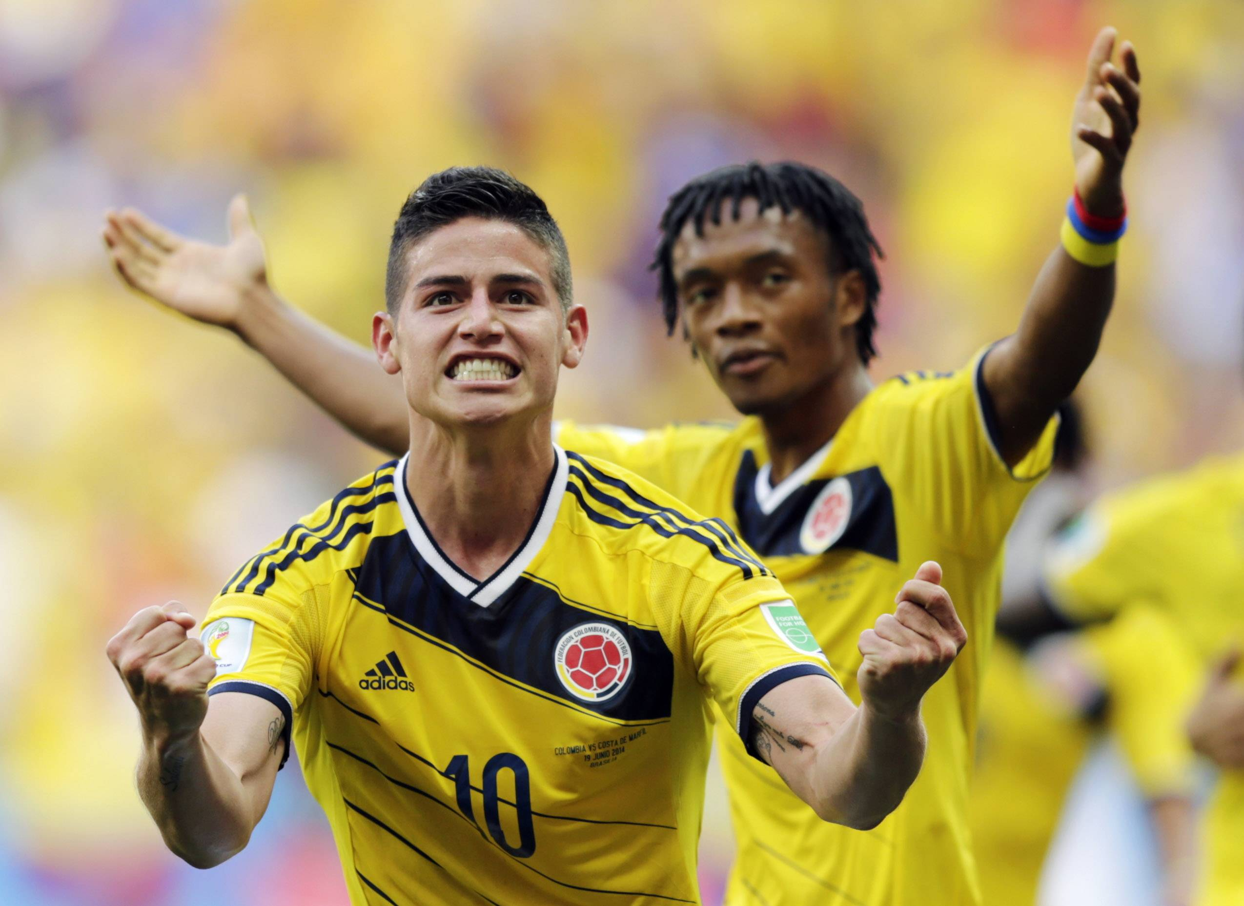 Colombia's James Rodriguez (10) celebrates with teammate Colombia's Juan Cuadrado Thursday after scoring his side's first goal against Ivory Coast during a Group C World Cup soccer match at the Estadio Nacional in Brasilia, Brazil.