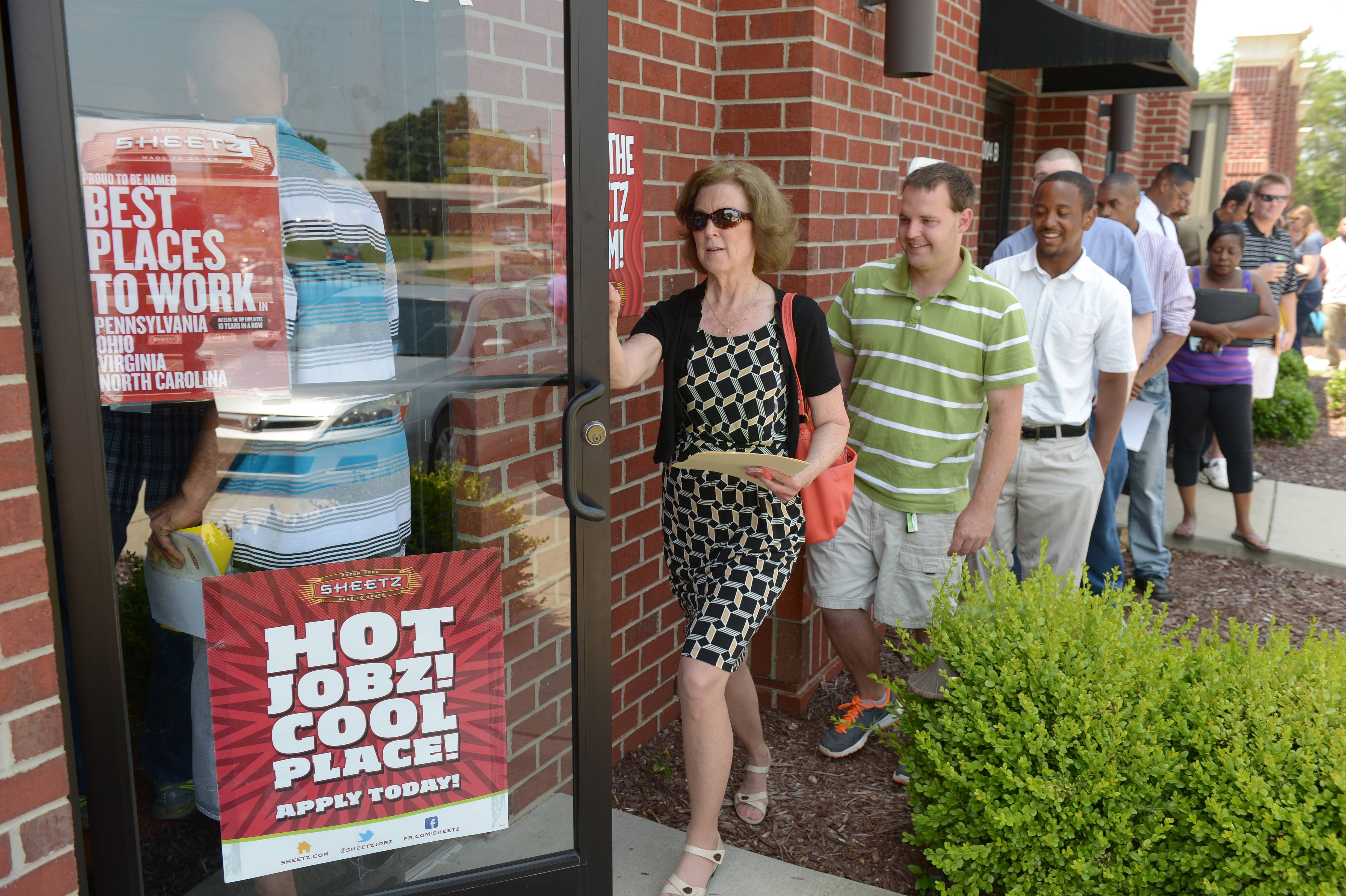 Job seekers attend a job fair held by Sheetz to staff their under-construction distribution center, in Burlington, N.C. The Labor Department reports the number of people who applied for unemployment benefits last week on Thursday, June 19, 2014.