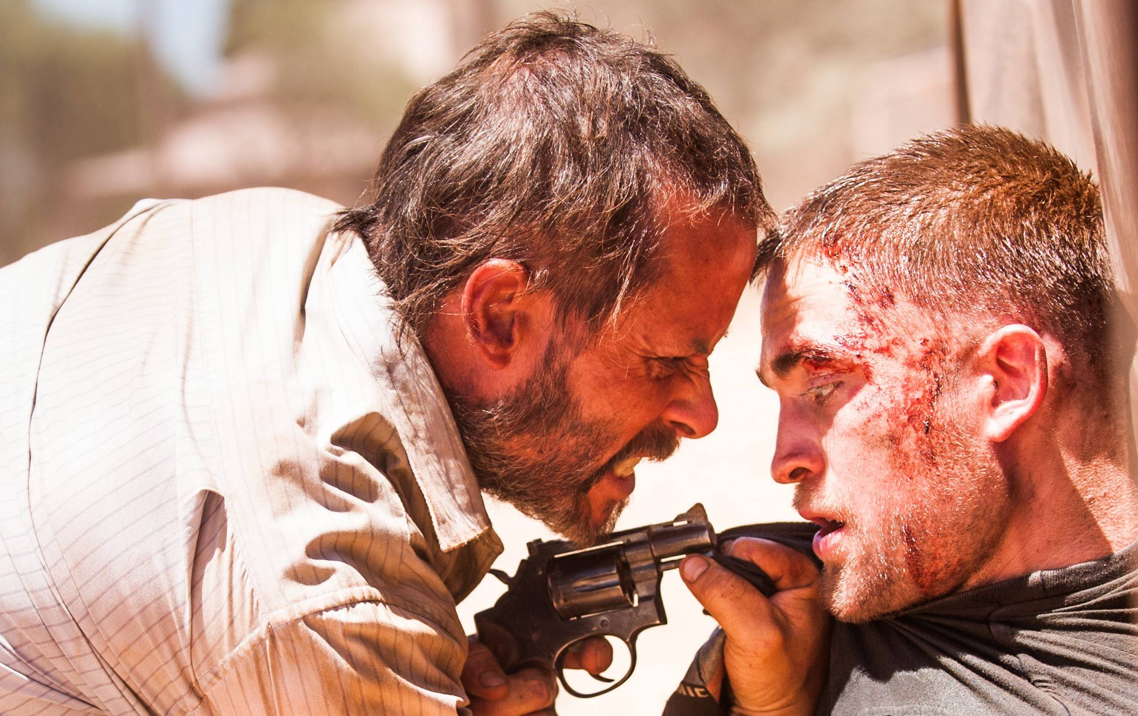 "Eric (Guy Pearce) roughs up Rey (Robert Pattinson) on a quest to recover a stolen car in the post-apocalyptic drama ""The Rover."""