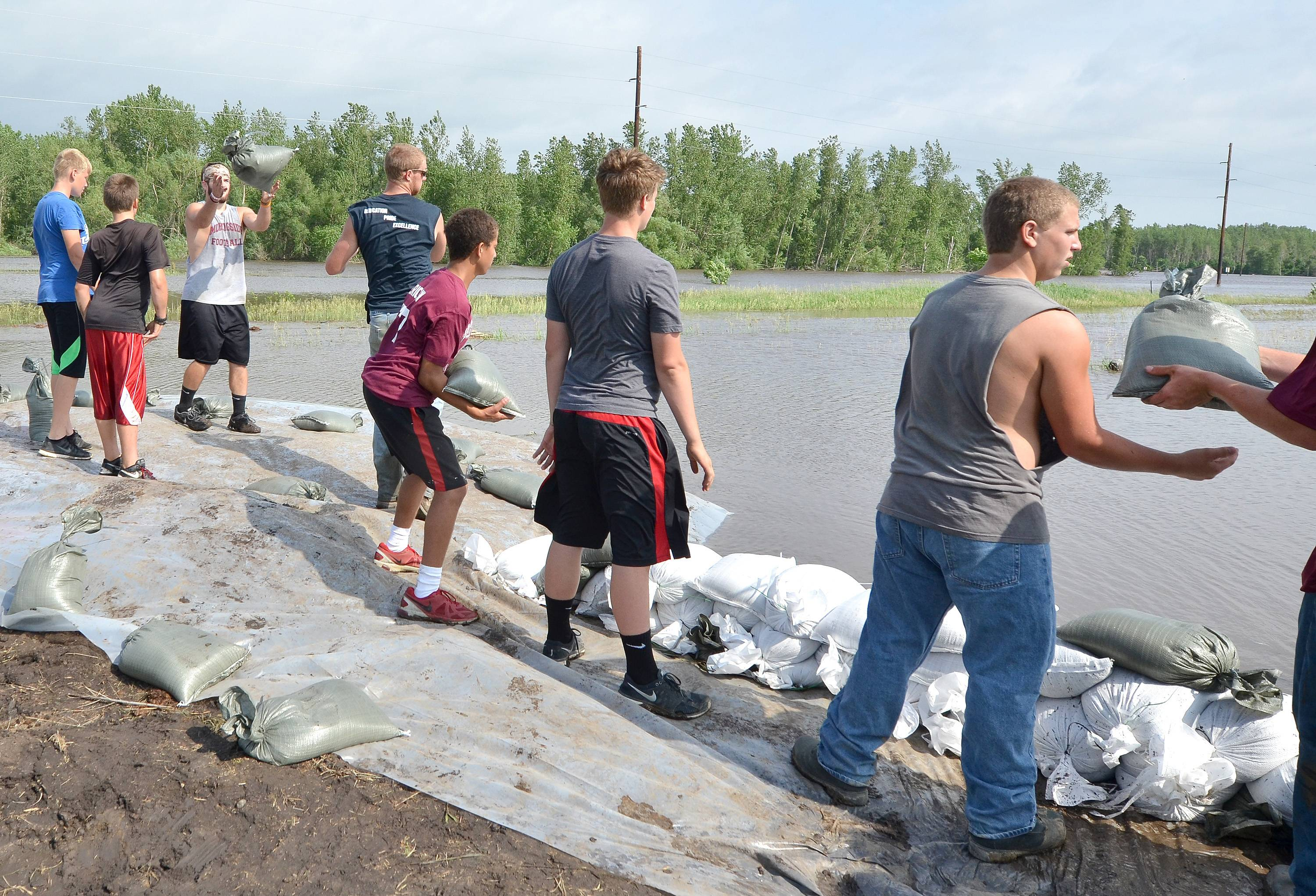 "Volunteers form a ""bucket brigade"" to pass sandbags Wednesday while working to fight floodwaters from the Big Sioux River in Akron, Iowa."