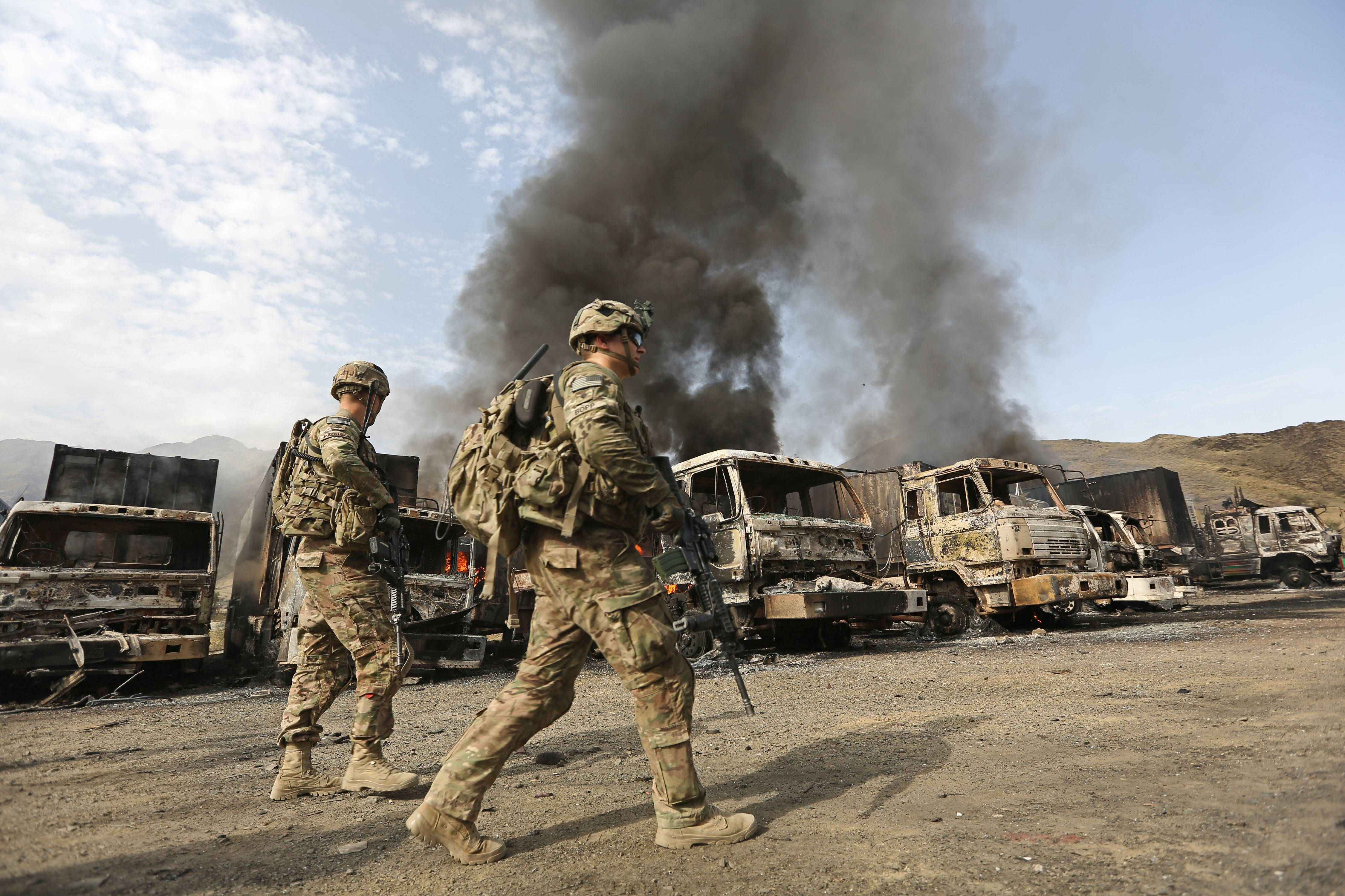U.S. soldiers investigate the scene of an suicide attack Thursday in the Torkham, Nangarhar province, Afghanistan. Senior Obama administration officials insist Afghanistan is not Iraq, with a population far more receptive to a continued U.S. presence and the promise of a new unity government.