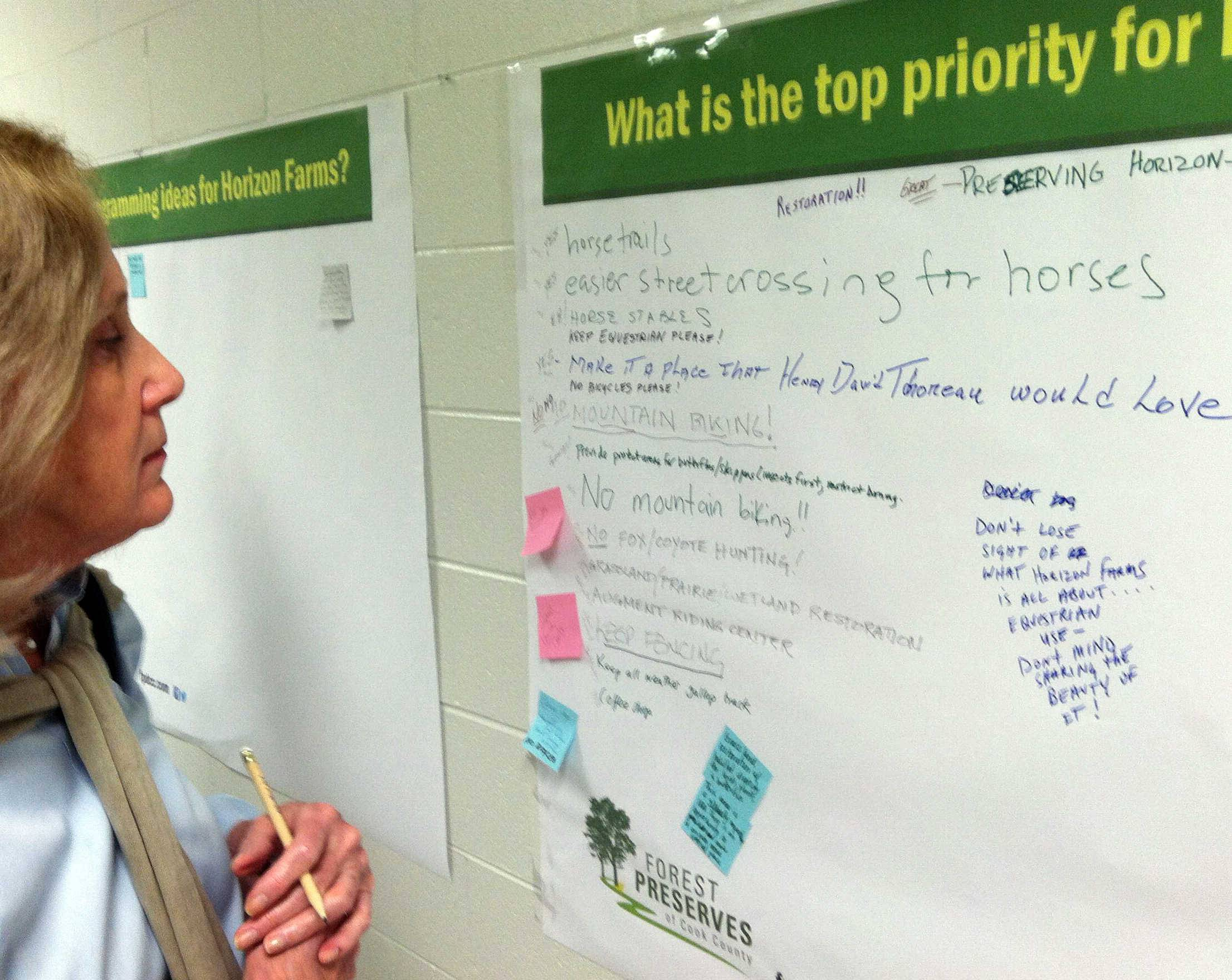 "Nancy White, of Barrington, reads comments left by other Barrington area residents on a poster board titled ""What is the top priority for Horizon Farms?"" at a public meeting held Wednesday night by the Cook County Forest Preserve District at Countryside Elementary School."