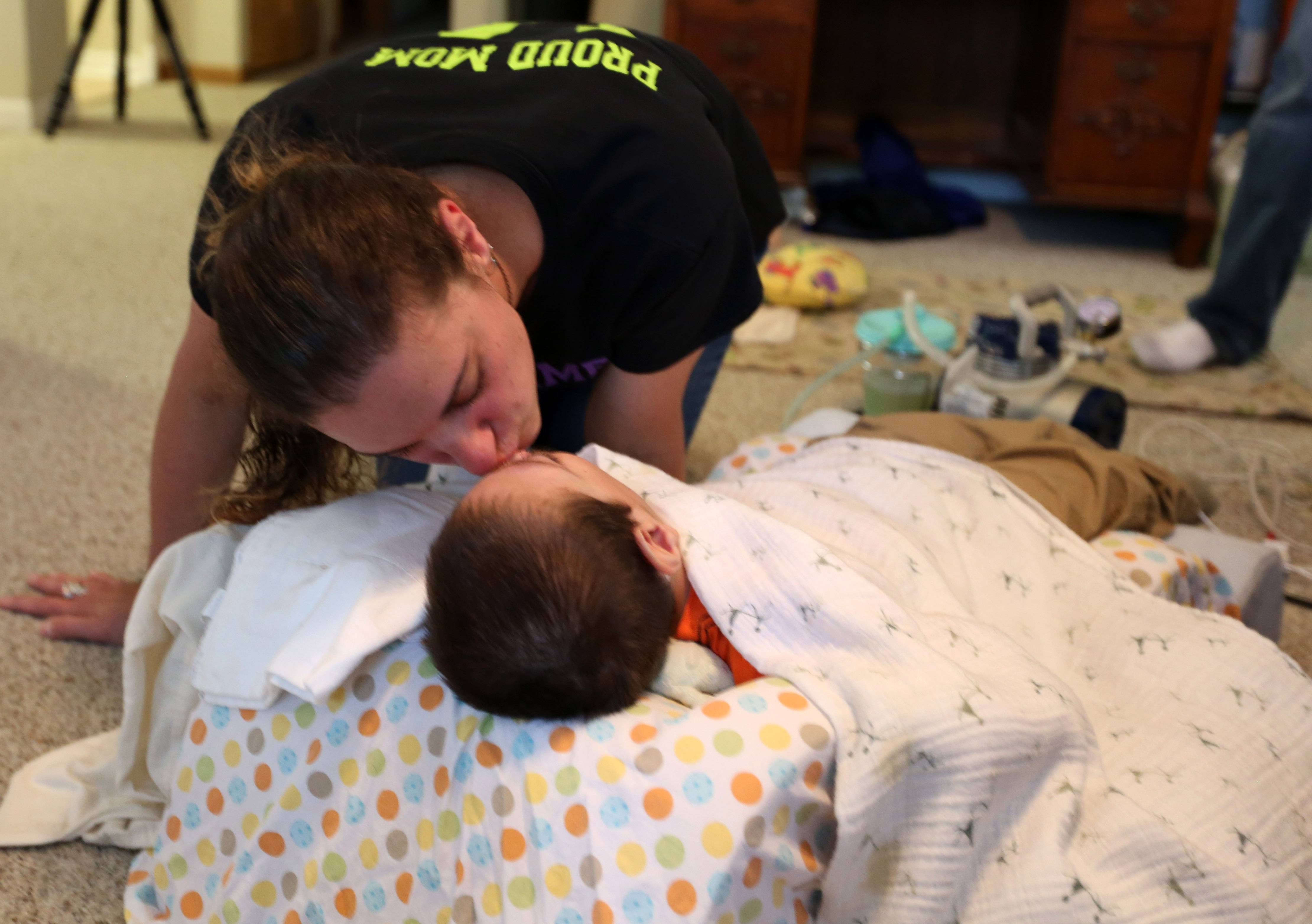 Celebrating the arrival of the family's new van, Stacy Fulkerson gives her son, James, a kiss in the driveway of their Schaumburg home. Suffering from a variety of disabilities, James, who turns 5 in August, outgrew his car seat in the family's old car.