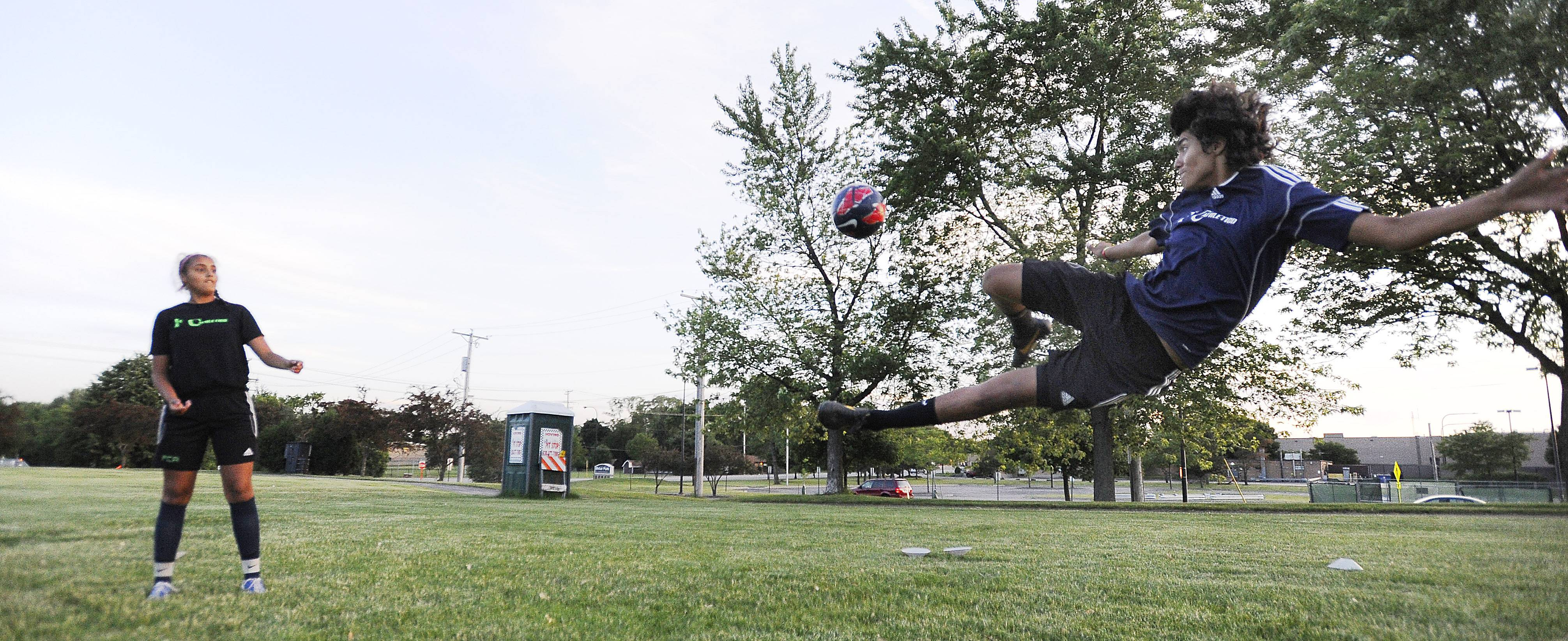 Wheeling's Luis Arreola, 15, leaps into the air to attempt a shot on goal as his sister, Alondra Arreola, 14, watches. The siblings both have their sights set on professional soccer careers and hope to one day represent the U.S. or Mexico in a World Cup.