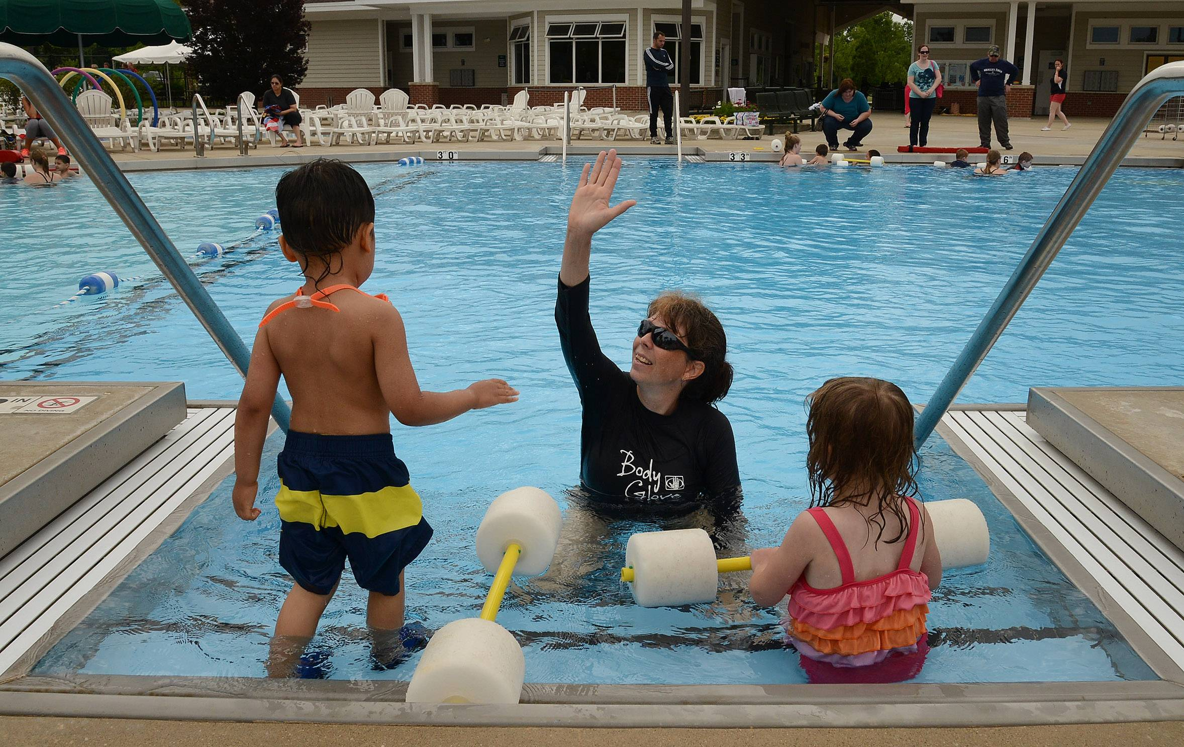 Swim instructor Jenni Delvecchio gives a high-five to Christopher Mitchell, 4, Gurnee, and Madeleine Strean, 5, Lindenhurst, after completion of their lesson during the World's Largest Swimming Lesson at the Hunt Club Park Aquatic Center in Gurnee.