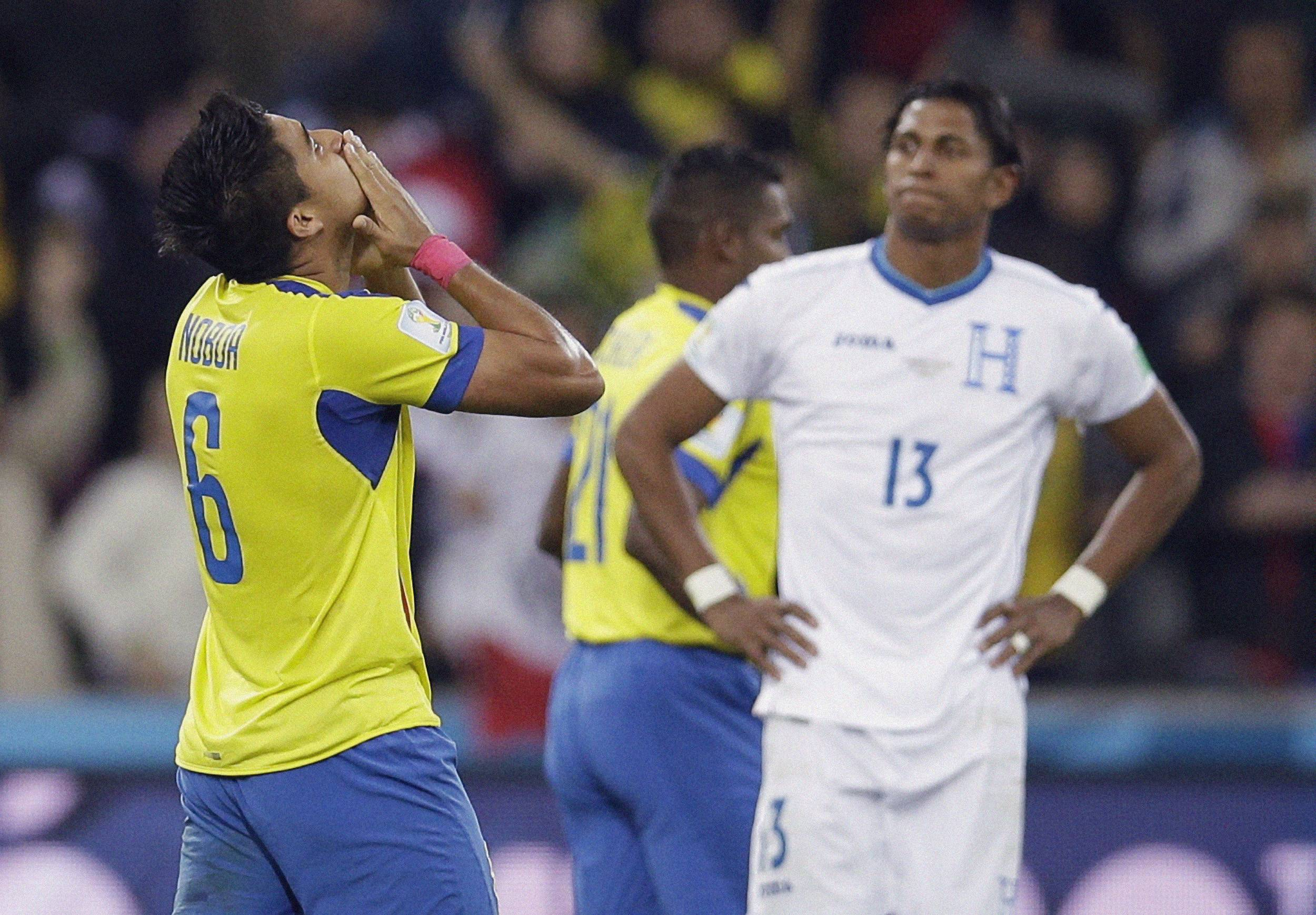 Ecuador's Cristhian Noboa celebrates at the final whistle as Honduras' Carlo Costly looks on after the group E World Cup soccer match at the Arena da Baixada in Curitiba, Brazil, Friday. Ecuador won the match 2-1.