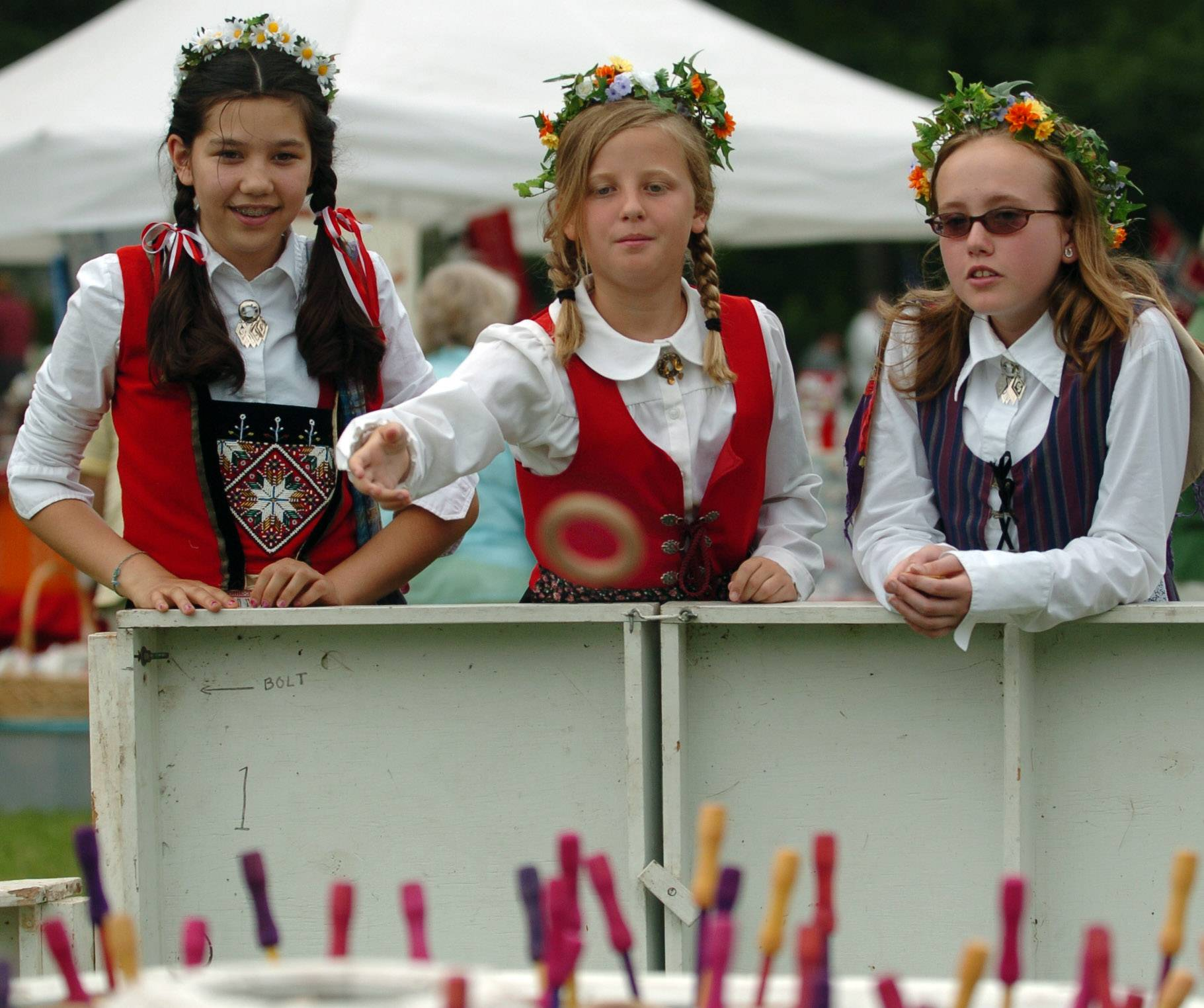 Anais Peterson, 13, of Batavia, left, and Lucy Smith, 11, of Geneva, right, watch Catherine Johnson, 11, of Huntley play the ring toss at the 100th annual celebration of the Swedish Day Midsommar Festival held at Good Templar Park in Geneva.